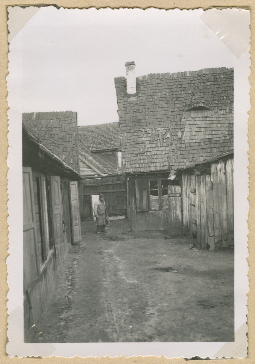 A bearded man in an apron stands in an otherwise deserted courtyard in an unidentified ghetto in Poland.