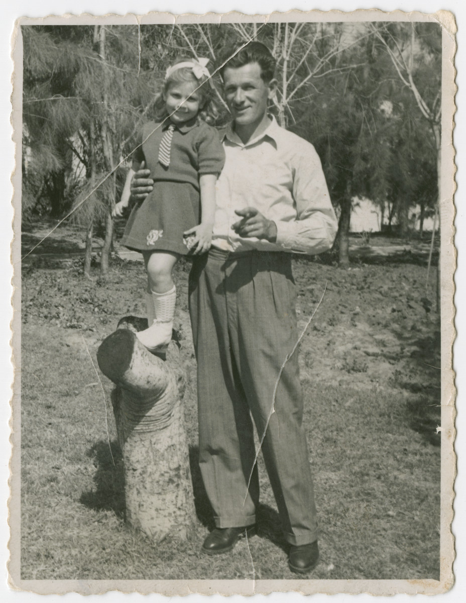 Yehuda Bielski poses with his daughter Nili who is standing on a tree stump.