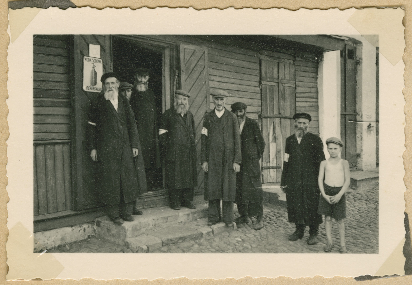 A group of Jewish men wearing armbands poses outside a building in Deblin-Irena
