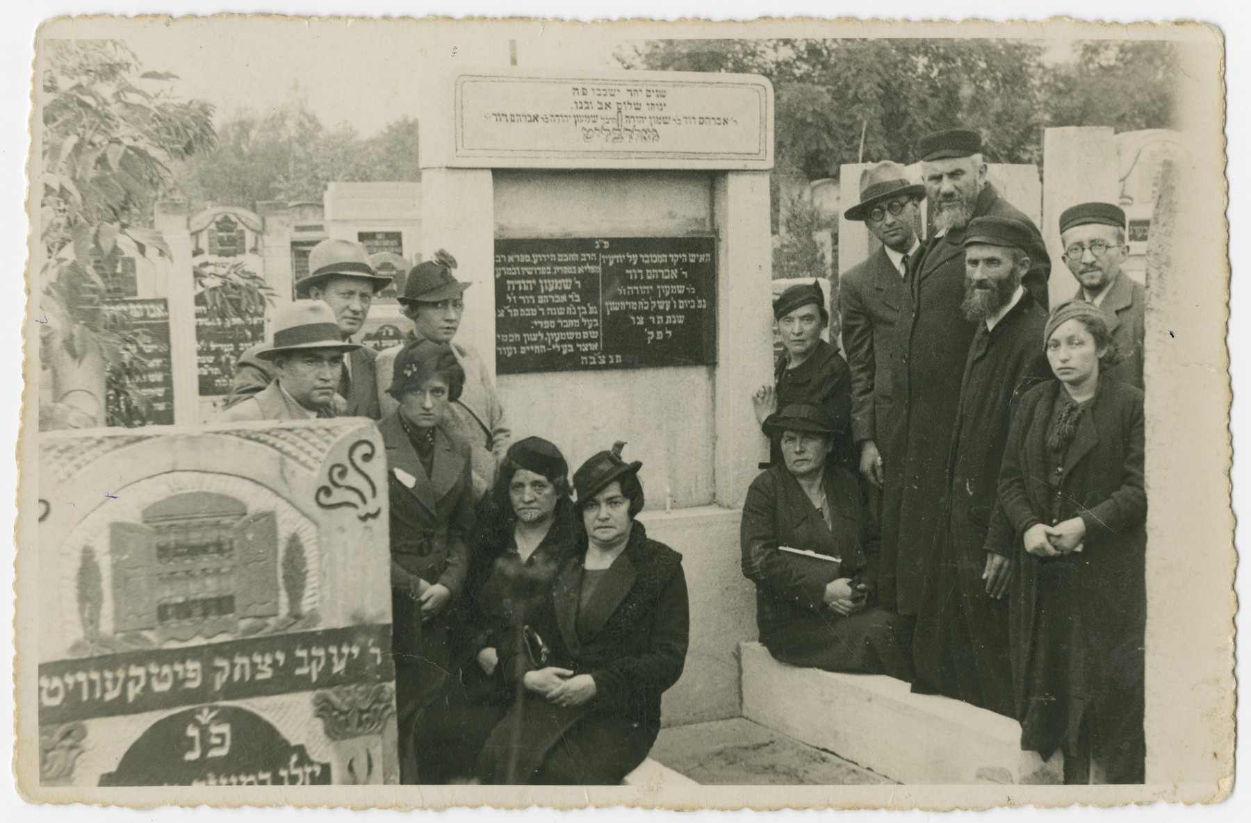 An extended Polish Jewish family gathers by a tombstone in the Jewish cemetery in Lodz.  Herschel Hudes (father of Lola Hudes Bielski), standing fourth from right and Necha Hudes (mother of Lola Hudes Bielski), seated first from left are pictured at the Lodz Cemetery shortly before the Holocaust.  All the people in the photo perished in the Holocaust.