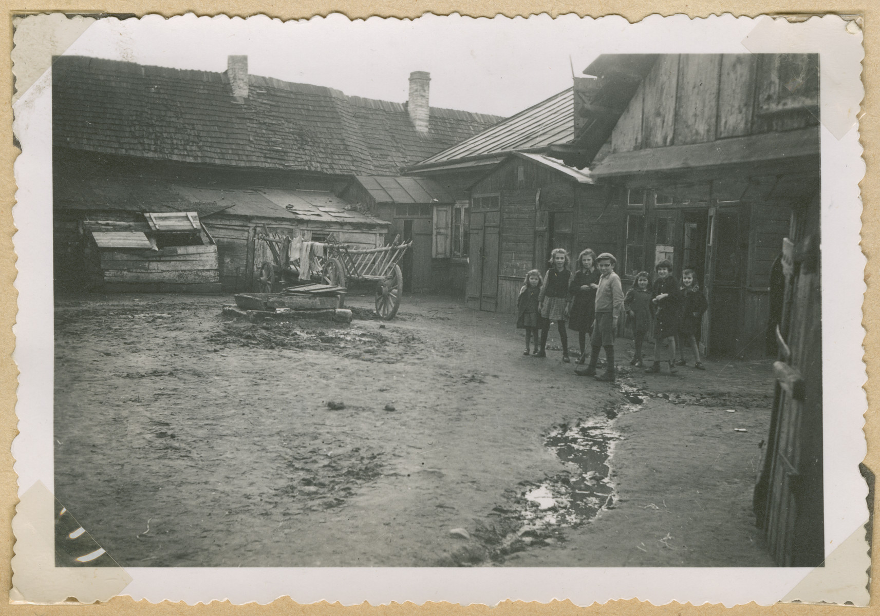 A group of children gathers in a courtyard in Poland.