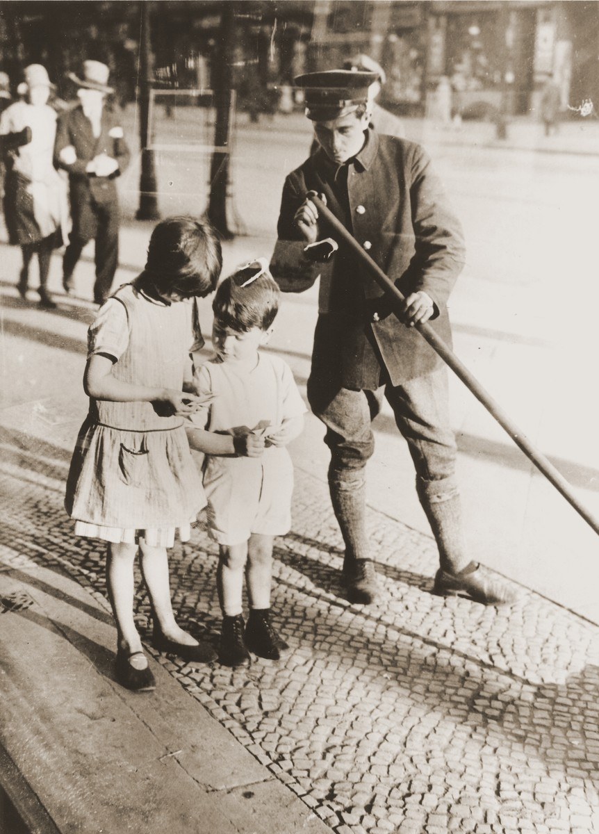 Two young children exchange cigarette coupons on the street in Berlin.    The little boy is the donor, Heinz Stephan Lewy, who is standing in front of his father's tobacco store.