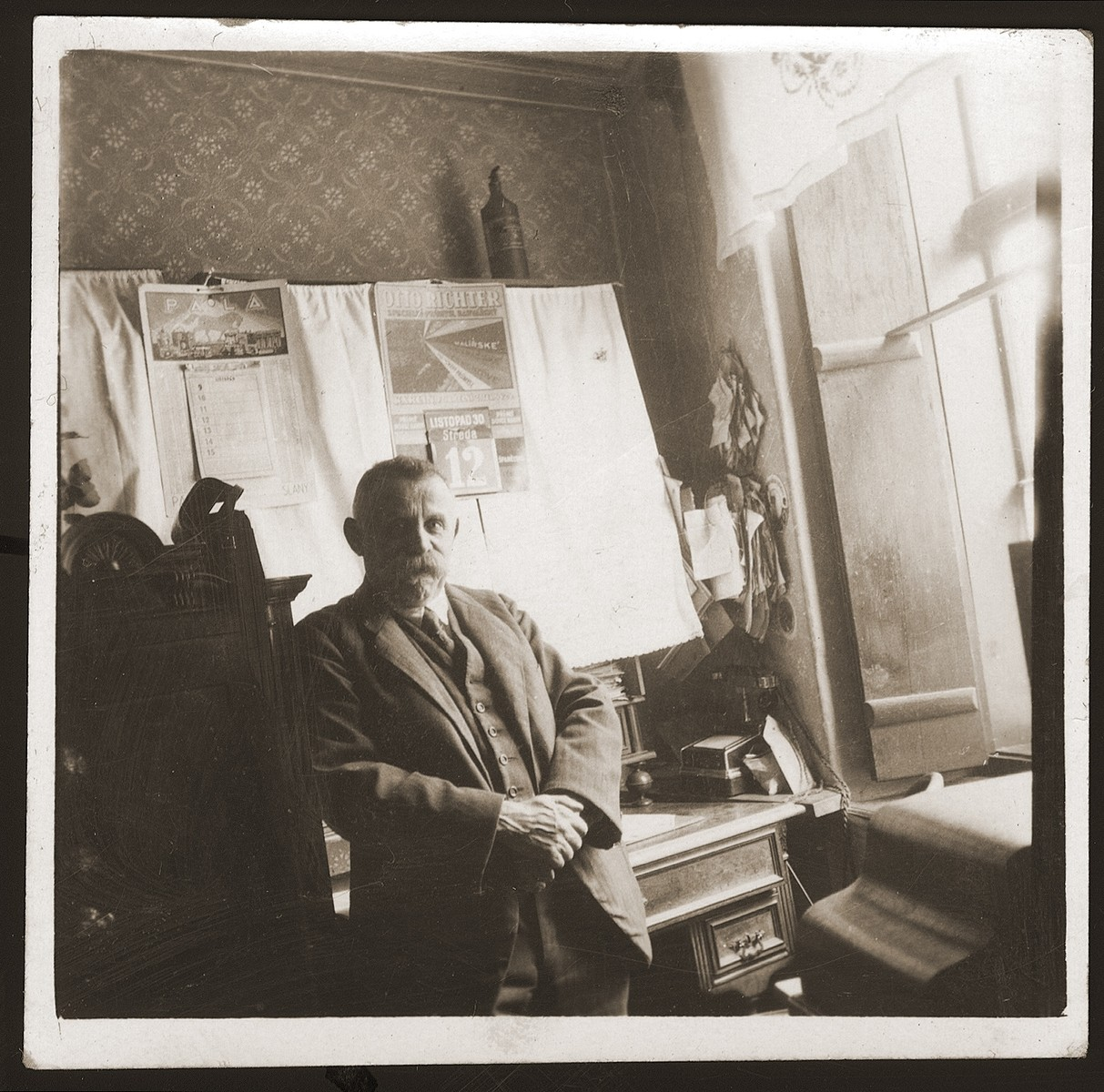Julius Goldstein stands in front of a desk in his general store.