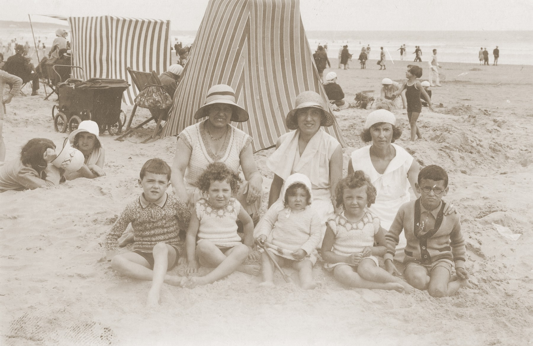 The Rubinsztejn family poses in front of a cabana on a beach in France.   Pictured are: Denise Grynberg, Eveline Grynberg, Dworja Rubinsztejn, Armand Rubinsztejn, and Chaya Grynberg Rubinsztejn.