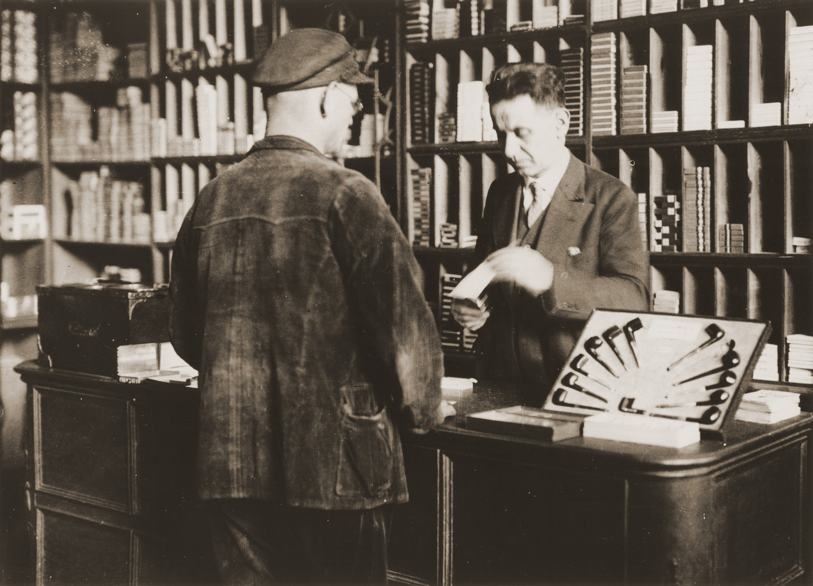Arthur Lewy confers with a customer in his tobacco shop in Berlin.