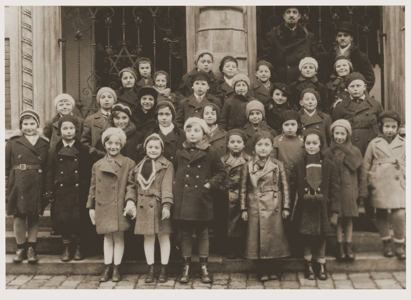 Afternoon Hebrew school class poses in front of the synagogue in Troppau (Opava).    Wearing leather coats in the front row are Leo and Milan Goldberger.  Their father, Cantor Eugene Goldberger is in the very back. In front of him is is brother-in-law and assistant, Gabor Berkovic.  Gabor became chief cantor following Eugene's move to Denmark.  He survived the war in hiding.