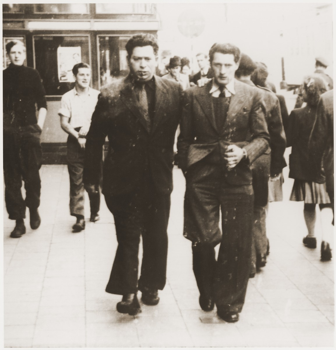 Two young Jewish men walk along a street in Antwerp, Belgium.  Pictured are Simon Rosenbaum (left) and his brother-in-law, Maurice Pomerantz (right).