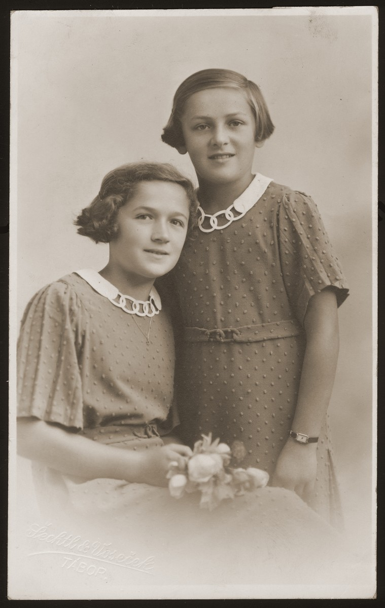 Studio portrait of Hana and Marie Spaeth wearing dresses with collars incorporating the Olympic rings.  The girls' dresses were designed in celebration of the 1936 Olympic games.    Hana and Marie (the donor's cousins) were the only children of Otto and Klara (Goldstein) Spaeth.  The family lived in Buchlovice, Moravia, where Otto ran a general store.  All four perished during the war.