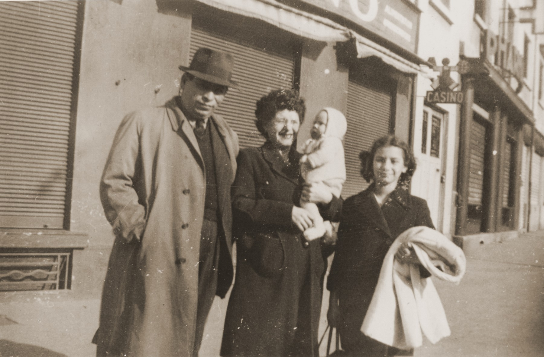 The Rosenbaum family living as non-Jews poses on street corner in Lyon.  Pictured from left to right are Simon, Esther holding her newborn daughter Michele and Frida Rosenbaum.