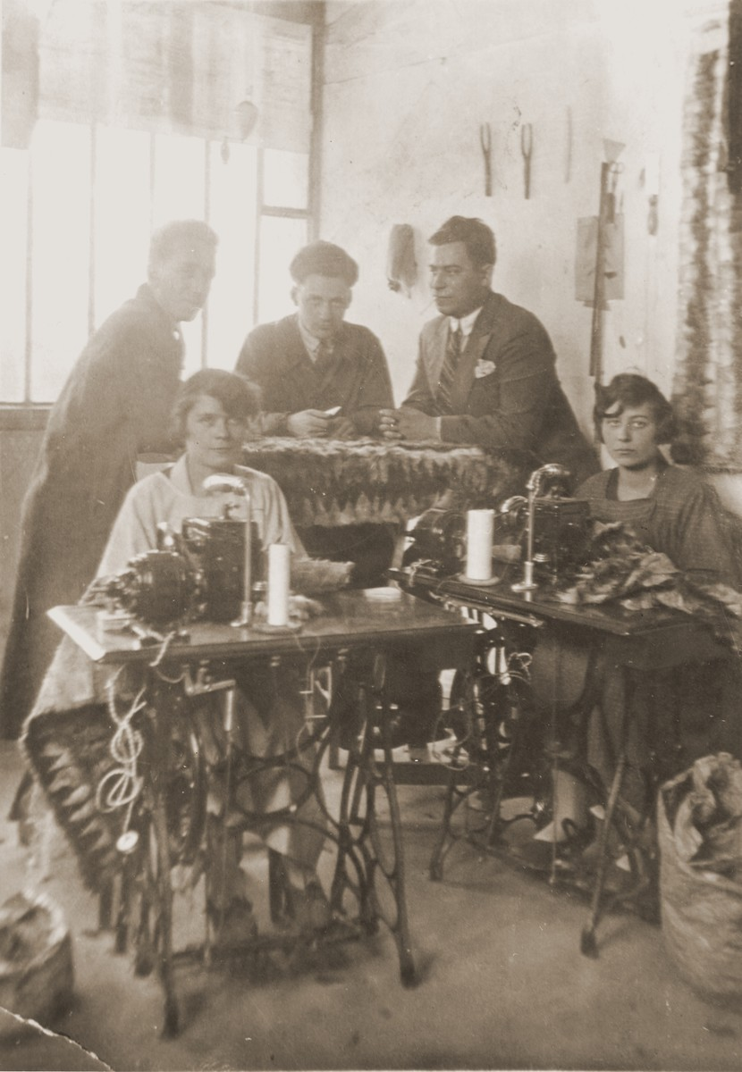 Simon Rosenbaum and his employees work in his furrier shop in Paris.    Pictured are Hela Feiglstock (seated on the left), Lea Klein, Simon's sister (seated on the right), Felix Feiglstock (back row, left), Hugo Feiglstock (back row, middle) and Simon Rosenbaum (back row, right).