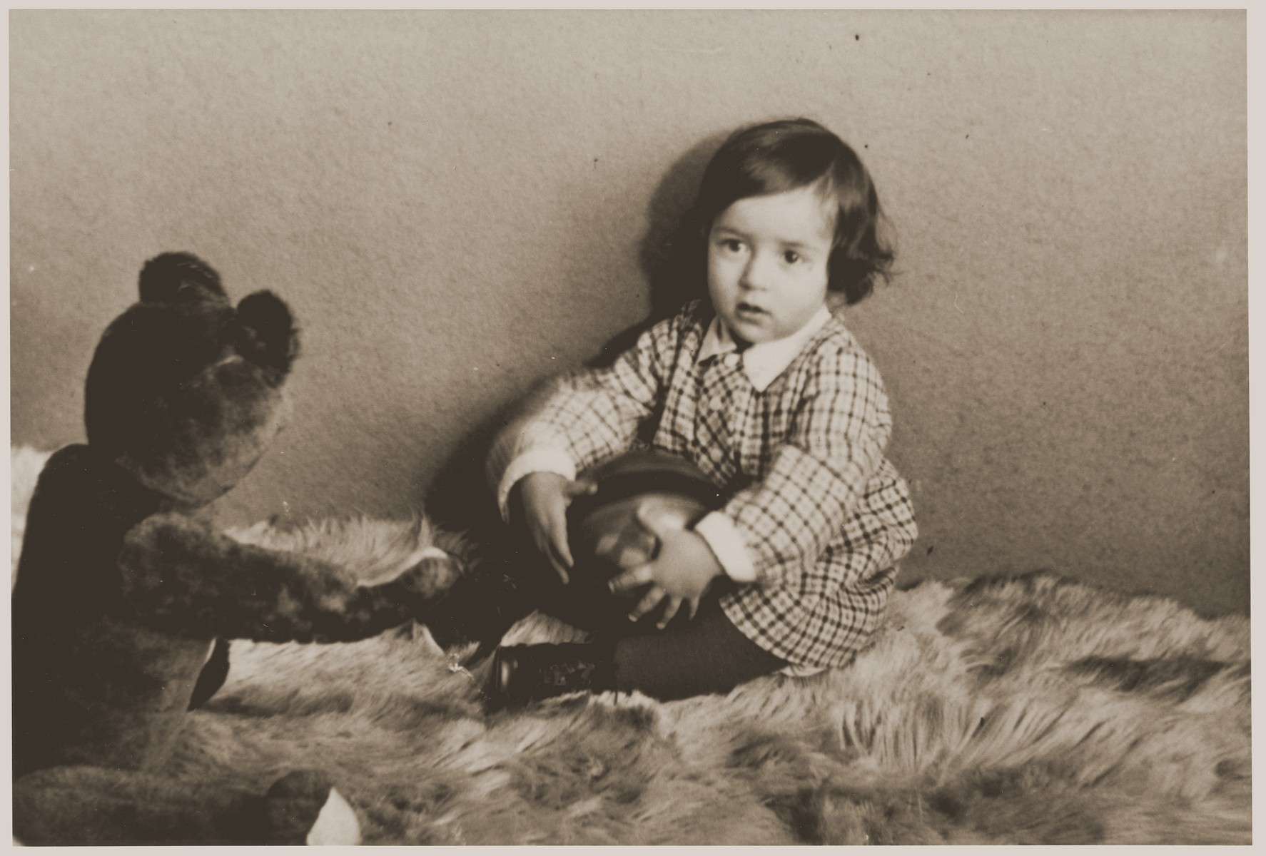 Portrait of one year old Suse Grunbaum with her teddy bear.