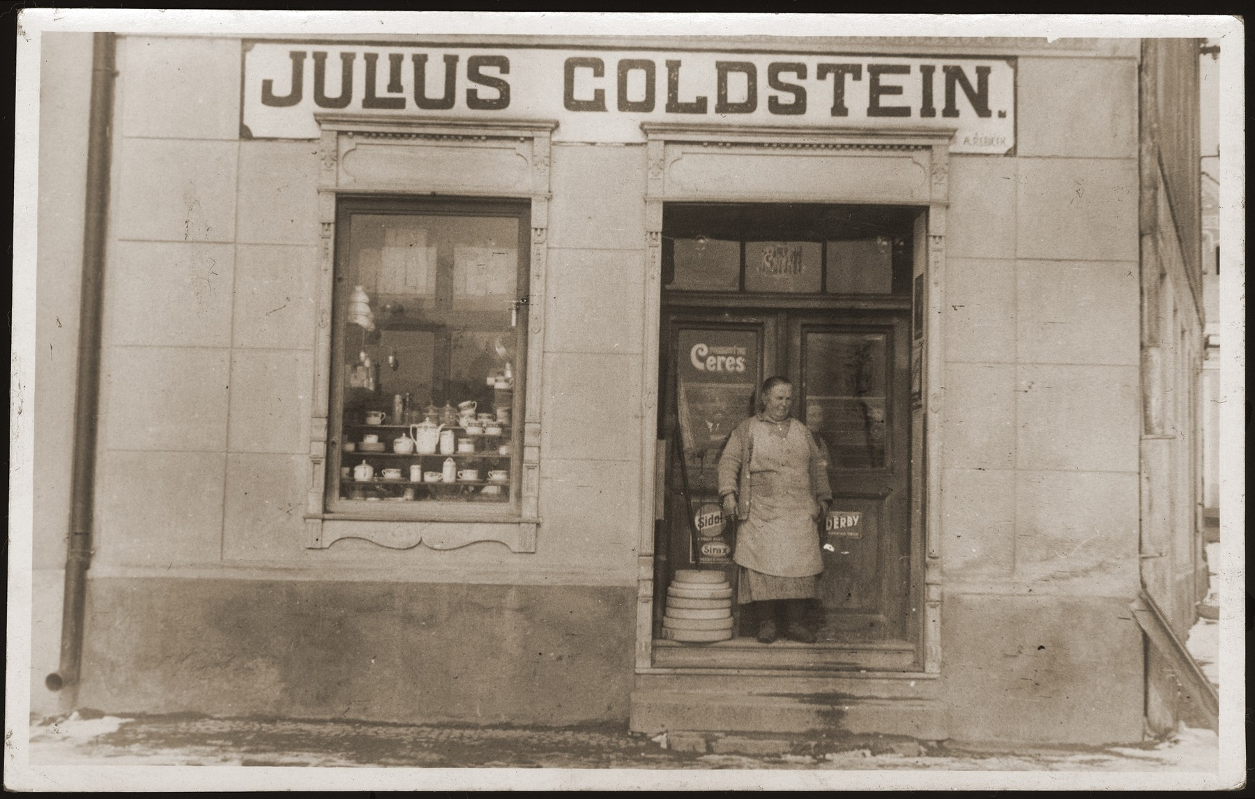Fanny Goldstein stands at the entrance to the family's general store in Sevetin, Czechoslovakia.    Julius Goldstein and one of his eight children are visible in the windows of the store.