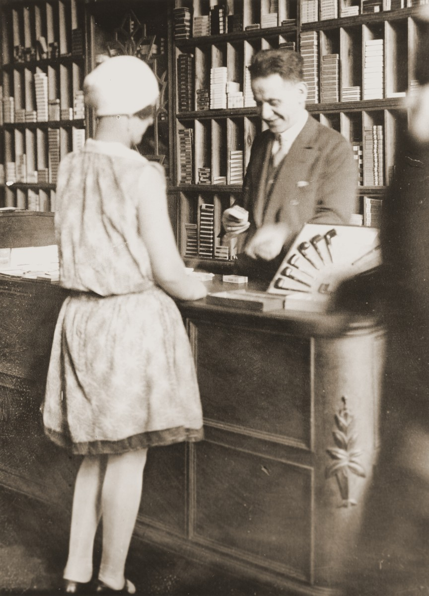 Arthur Lewy confers with a customer in his tobacco store in Berlin.