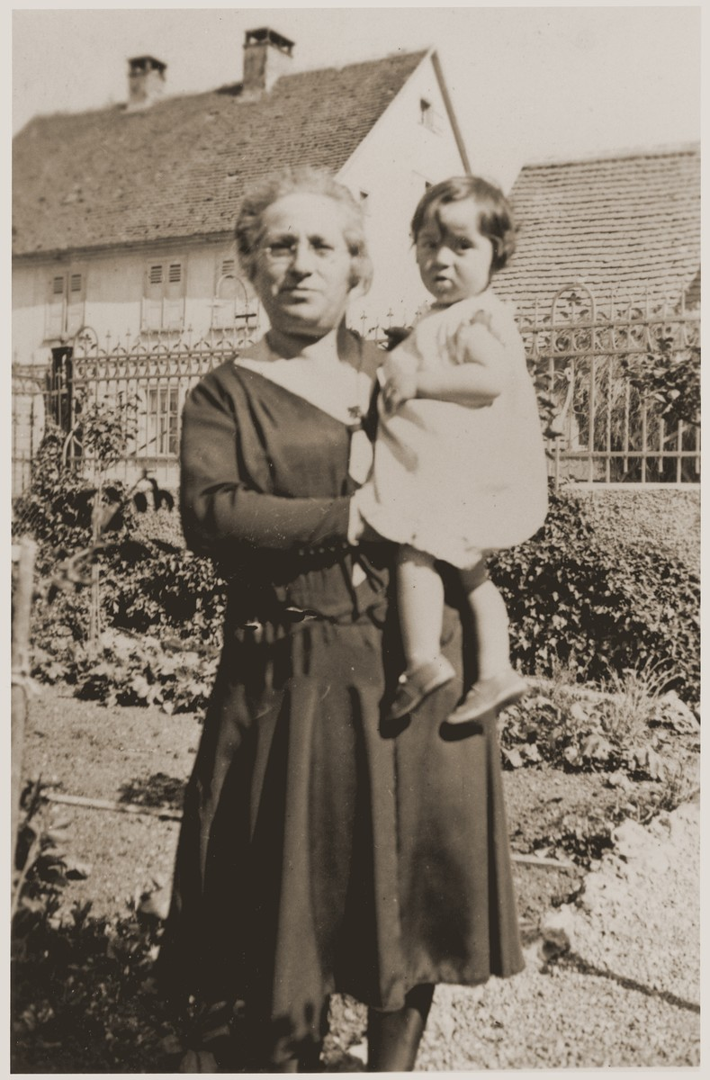 Suse Grunbaum is held by her great-aunt,  Adele Kahn in front of the home of her grandmother, Frieda Kahn.