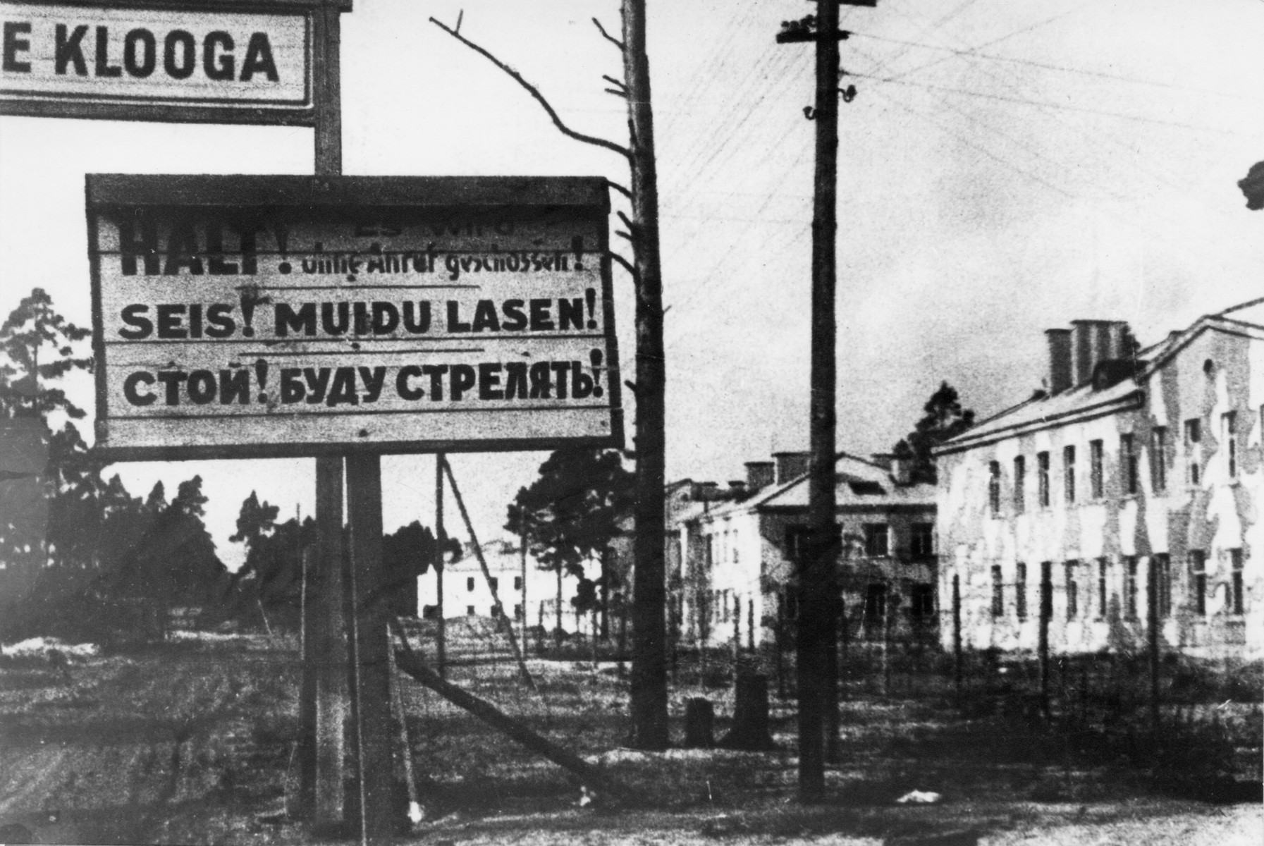 "A warning sign in German, Russian and Estonian posted at the entrance to the Klooga concentration camp that reads: ""Stop! You will be shot without warning!"""