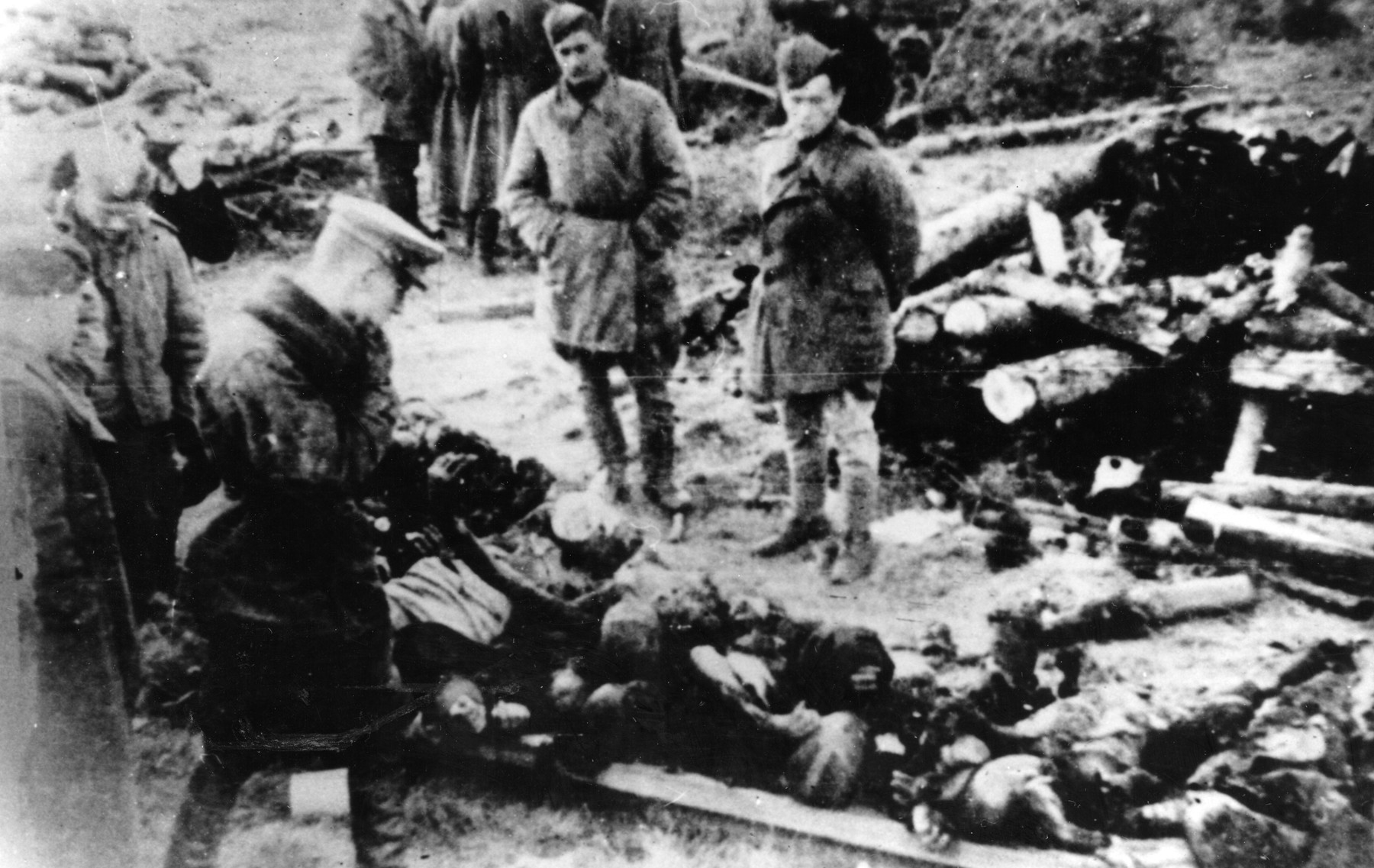 Soviet troops view the bodies of prisoners from the Klooga concentration camp that have been stacked on a pyre.