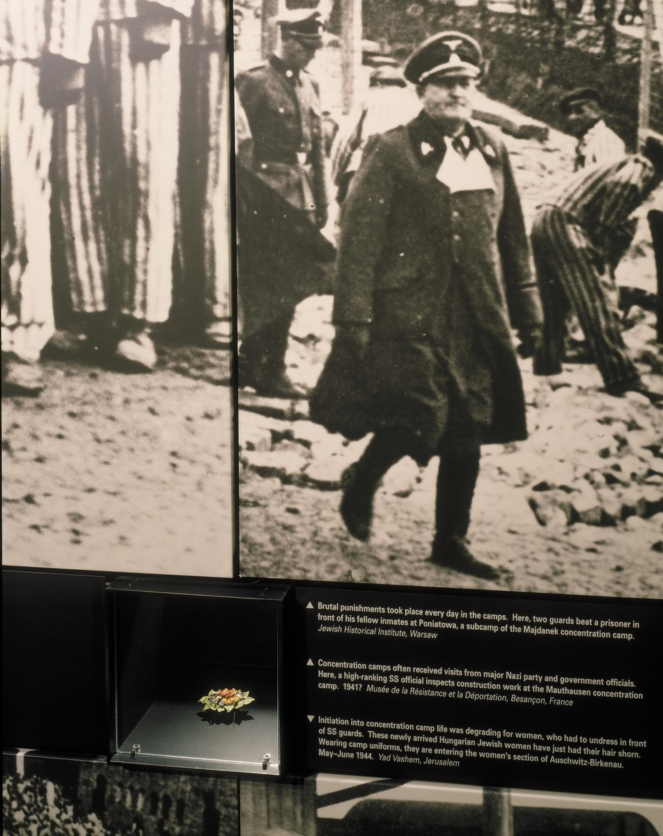 "Detail of the ""In the Camps"" photo mural and brooch displayed on the third floor of the permanent exhibition at the U.S. Holocaust Memorial Museum.  The photograph shows an SS official inspecting construction work at the Mauthausen concentration camp.  The brooch was made by a Bergen-Belsen inmate in 1943."
