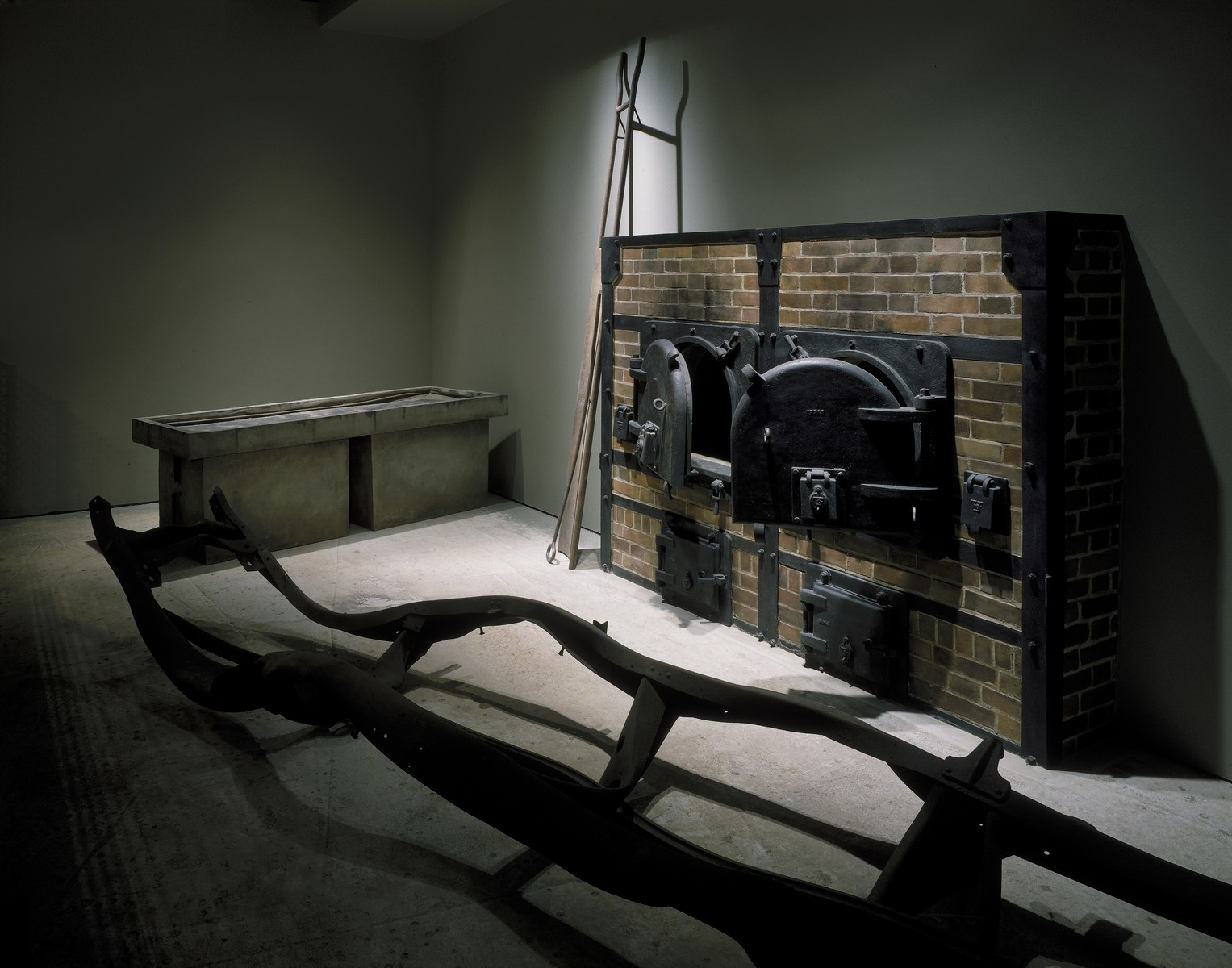 The dissecting table, casting of crematoria doors, crematoria implements, and twisted truck chassis on display in the third floor tower room of the permanent exhibition at the U.S. Holocaust Memorial Museum.