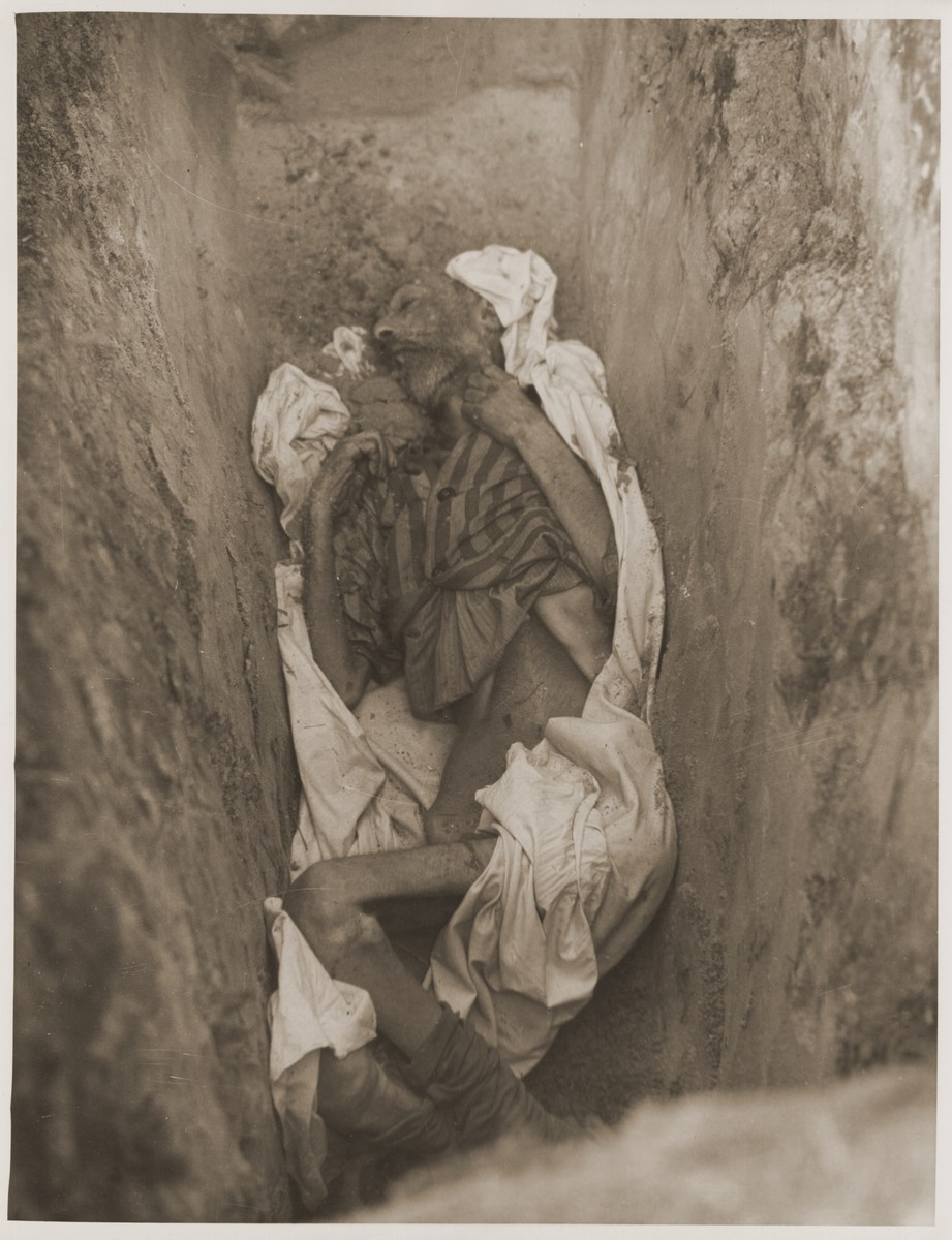 The emaciated corpse of a prisoner that is partially wrapped in a sheet, lies at the bottom of a grave in the newly liberated Woebbelin concentration camp.
