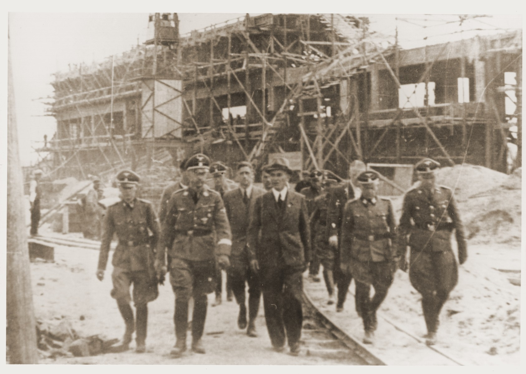 Reichsfuehrer SS Heinrich Himmler tours the Monowitz-Buna building site in the company of SS officers and IG Farben engineers.   Pictured in the front row from left to right are: Rudolf Brandt, Heinrich Himmler, Max Faust, unknown and Rudolf Hoess.  Faust, who was an IG Farben engineer, was the head of building operations at Monowitz-Buna.