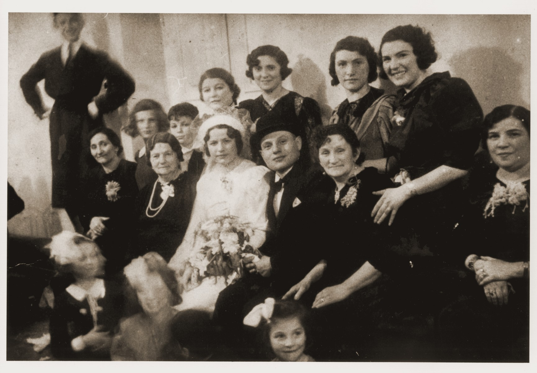 Group portrait of family and friends at the wedding of Bracha Broncia Rotsztajn and Mr. Kratka.    Standing on the far left is Aaron Rotsztajn (the donor's paternal uncle, who escaped Poland to Palestine in 1941).  In the second row, second from the left, is Roma Rotsztajn (the donor), her brother, Dawid; an aunt; Bracha Rotsztajn; Rozia Rotsztajn and Ela Rotsztajn.  In the front row, second from the left is Malka Rotsztajn (the donor's great grandmother); Bracha and her husband and Dwora (Rozmaryn) Rotsztajn (the donor's grandmother).  Aaron and Roma were the only survivors of this group.