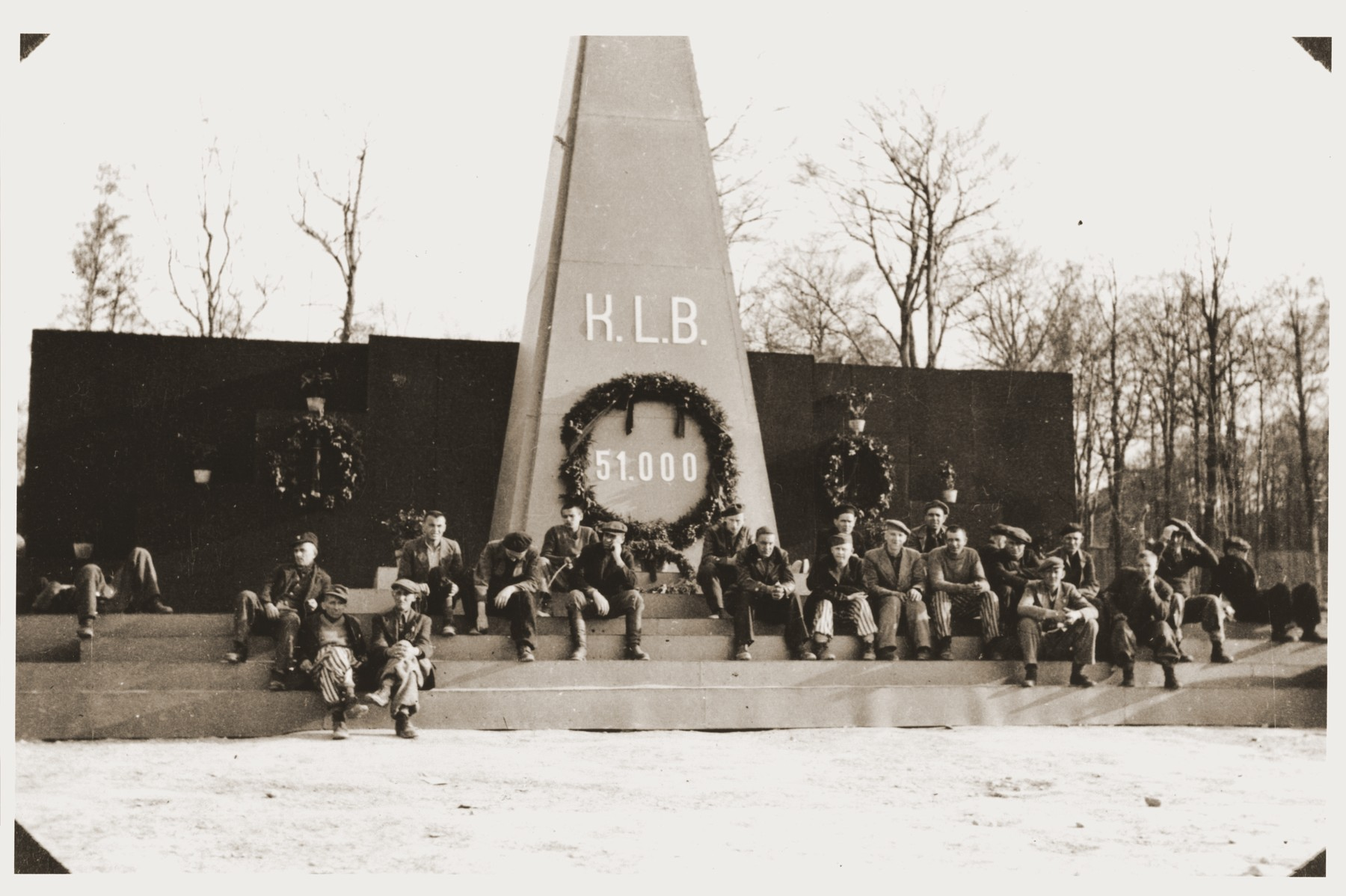 Displaced persons sit in front of a monument erected to the memory of the 51,000 victims of Buchenwald.