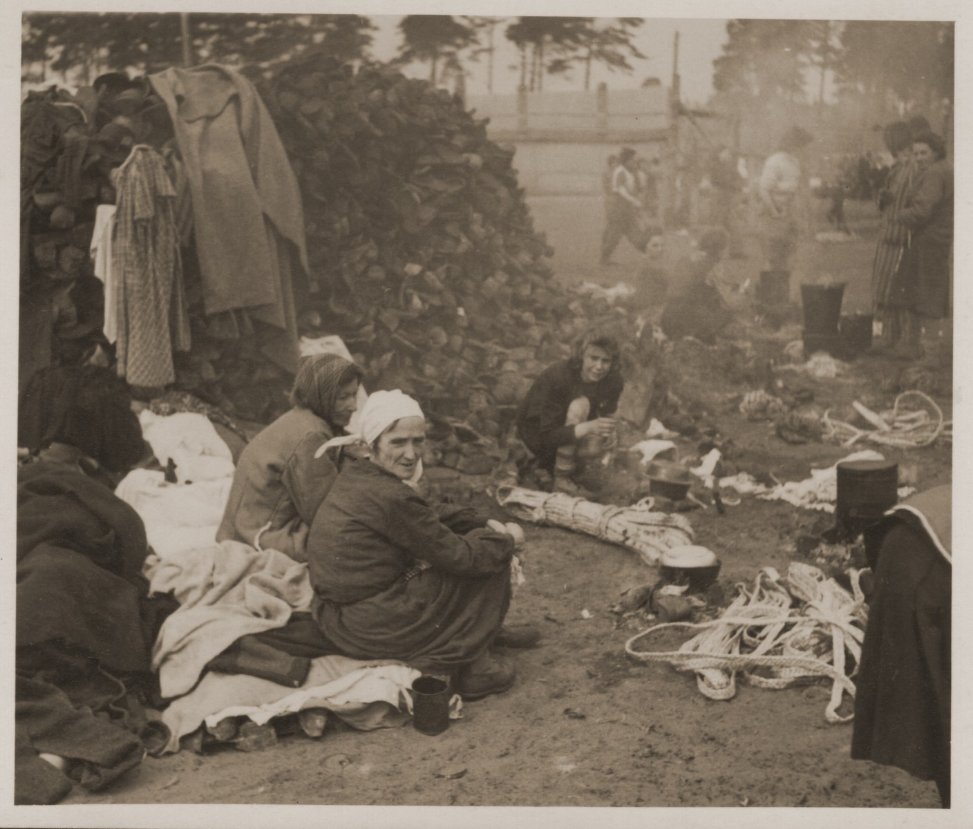 Survivors in Bergen-Belsen cook over an open fire next to a mound of shoes.