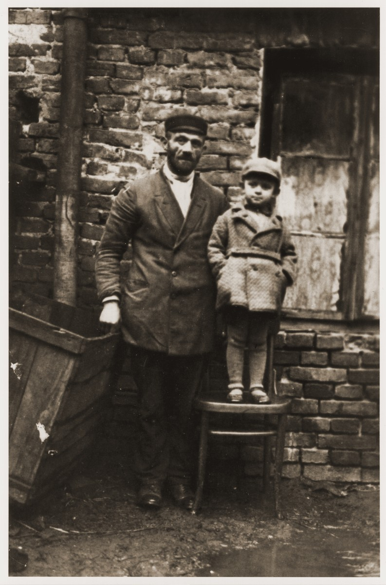 Hirsch Glicenstein poses with his young nephew, Leo Grinberg, in front of a brick house in Kalisz.