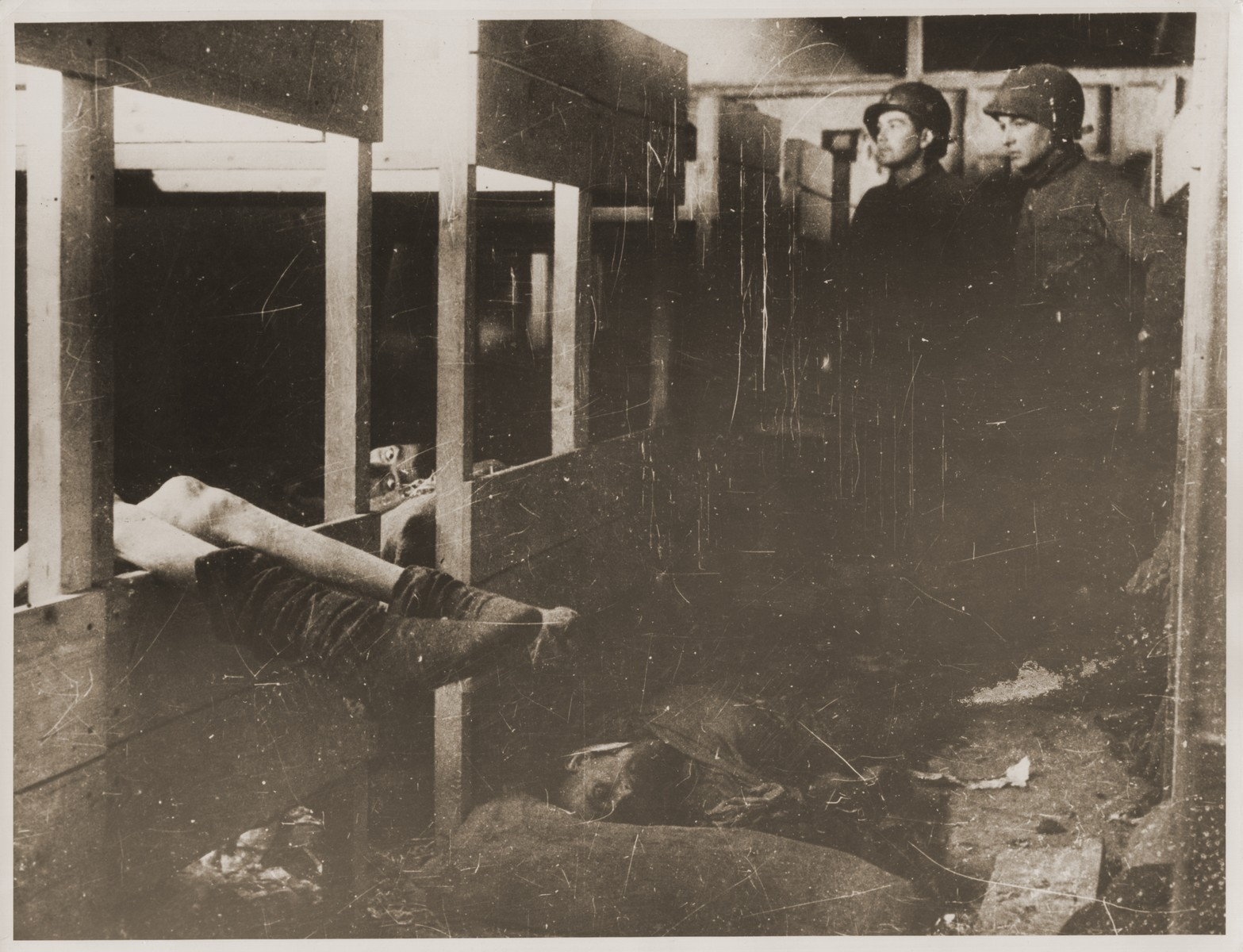 American troops inspect a barracks in Dora-Mittelbau soon after the liberation.   Two survivors lie in bunks, while corpses lie on the floor.