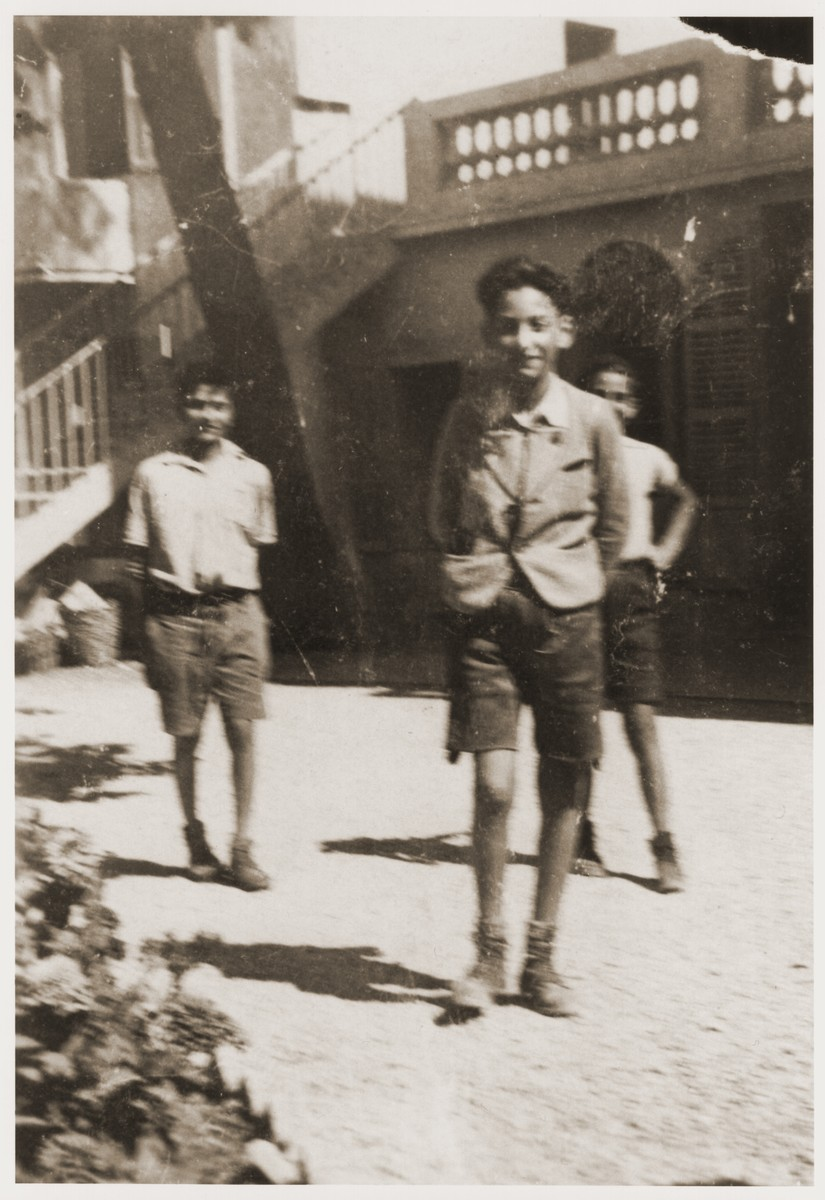 Three Jewish refugees youths stand in the courtyard of the Hotel Bompard transit camp in Marseilles.   Kurt Leuchter is pictured in the foreground.