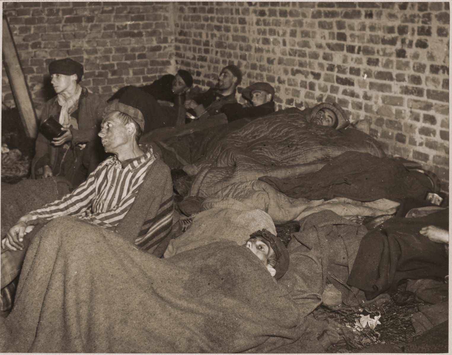 Survivors wrapped in blankets lie on the floor of a barracks in Woebbelin.  The boy in the upper left wearing a black cap is Geae Meissels (age 12-13).