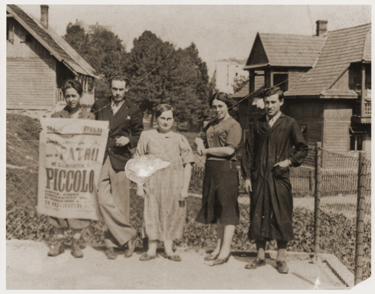Berl Moncznik (right) poses outside with members of the Checkinski family, who owned the print shop in Krynica where he worked.    The poster they hold was printed in their shop.