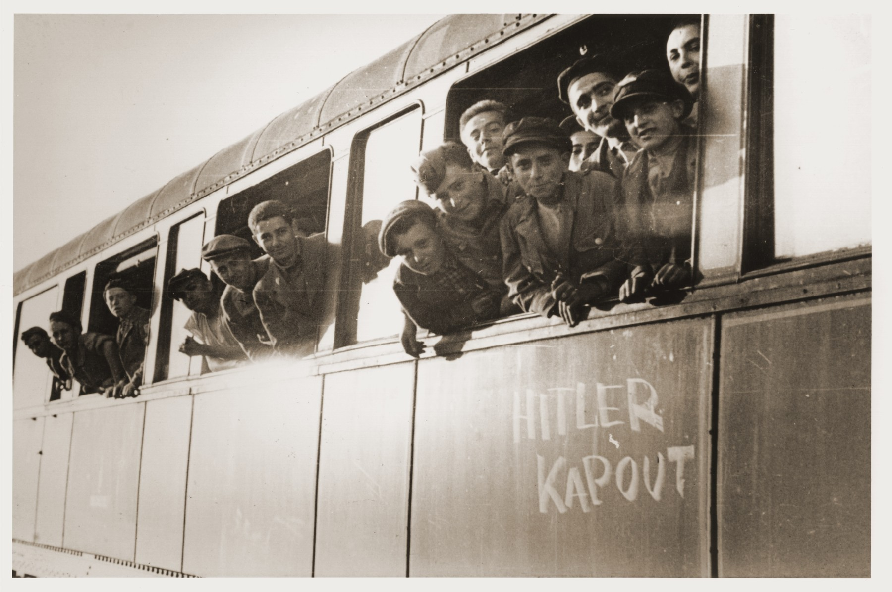 "Jewish youth liberated at Buchenwald lean out the windows of a train, as it pulls away from the station.  The train, which has been marked with the phrase ""Hitler kapout  [sic]"" [Hitler is finished], will transport the children to an OSE (Oeuvre de Secours aux Enfants) home in Ecouis, France."