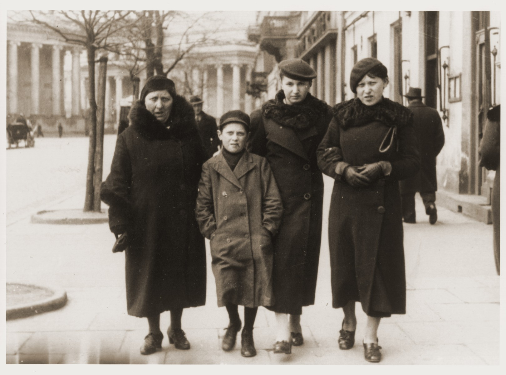 Members of the Tenenbaum family walk along the streets of Warsaw.  Pictured from left to right are Anka Leah, Szmuel, a cousin, and Nechama Tenenbaum.