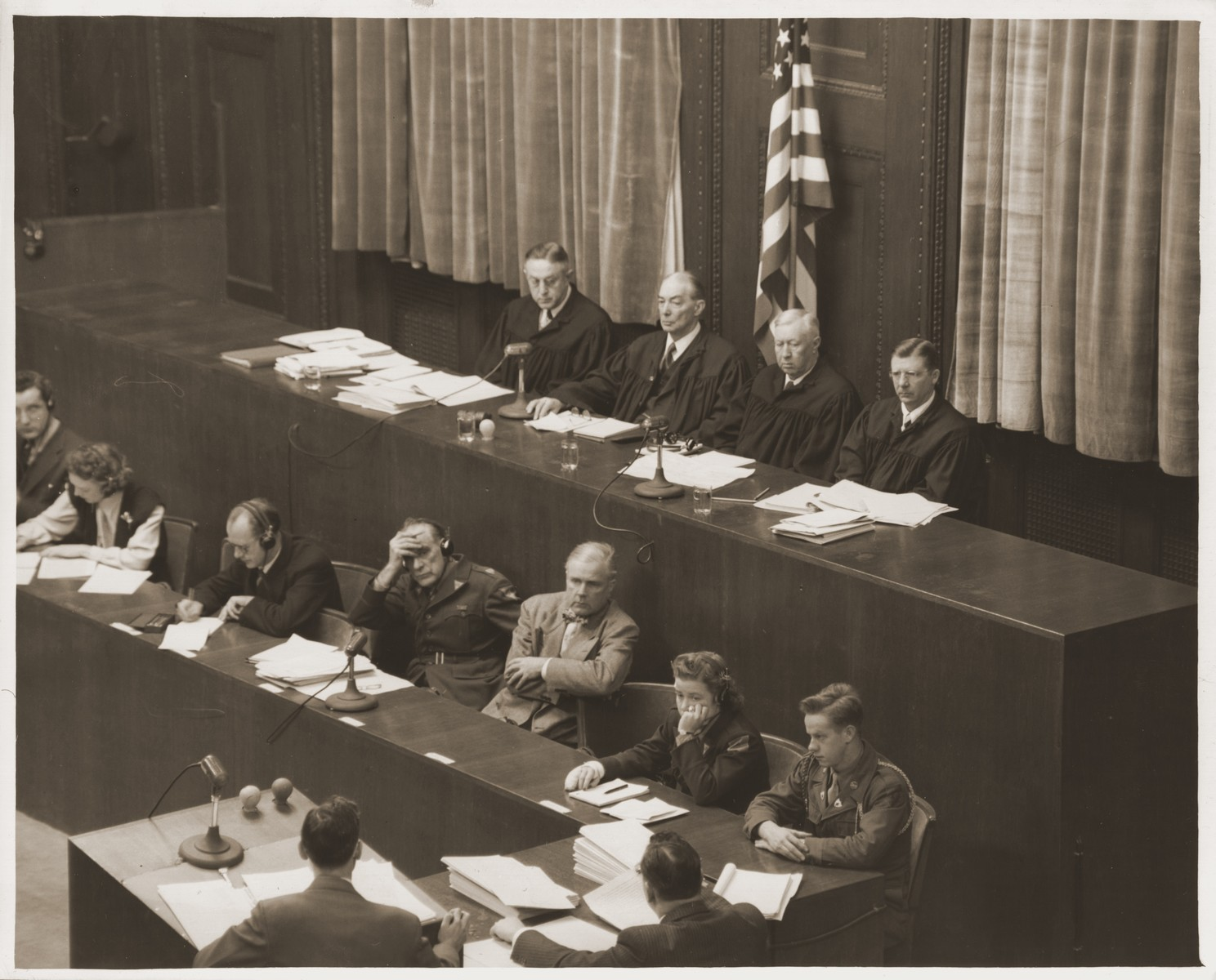 The judges of the Military Tribunal I during a session of the Medical Case (Doctors') Trial in Nuremberg.    Sitting from left to right along the top are Harold L. Sebring, Walter B. Beals, Johnson T. Crawford, and Victor C. Swearington.  Below them are the court reporters.