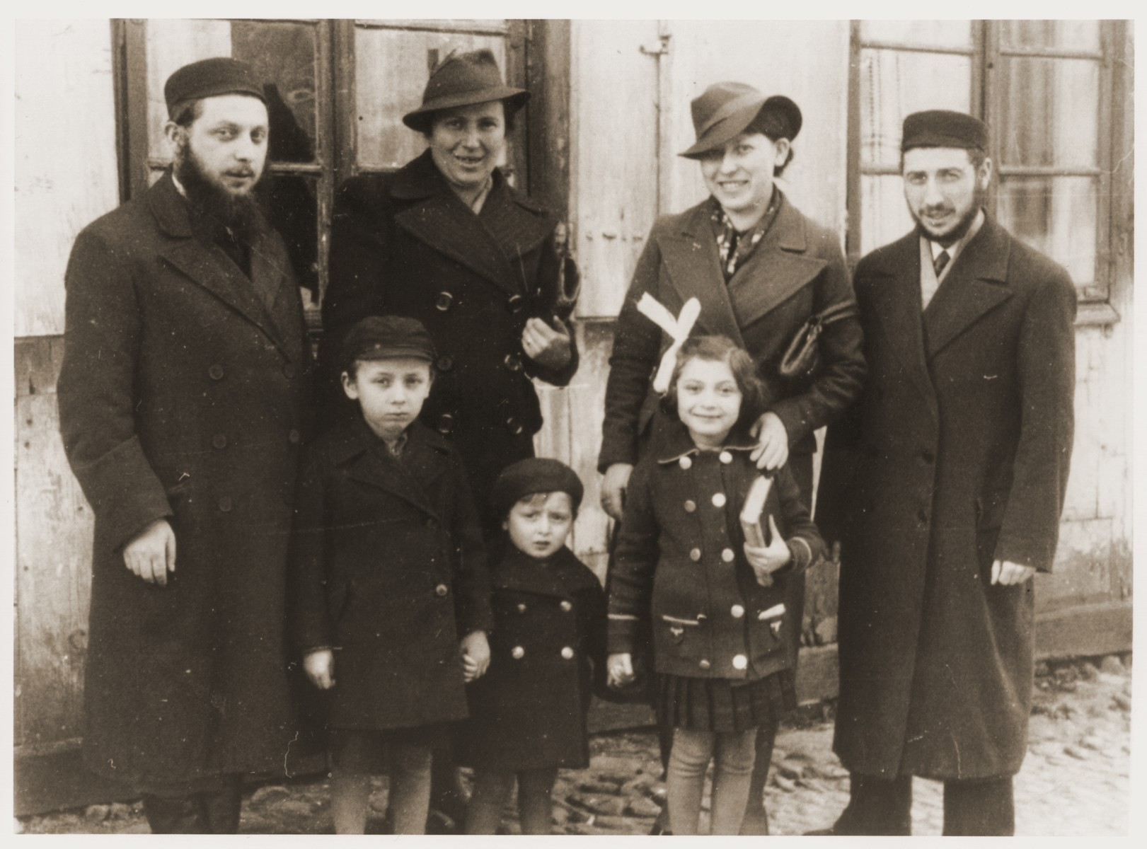 Portrait of the Tenenbaum in front of a house in Warsaw.  Pictured standing (from left to right) are: Pinchas Tenenbaum and his wife, Fajgl (Warszawska)Tenenbaum; Nechama and Srulik Tenenbaum.  In front are Pinchas' three children.