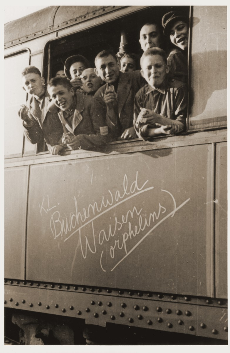 "Jewish youth liberated at Buchenwald lean out the window of a train, as it pulls away from the station.  The train, which has been marked with the words ""KL Buchenwald Waisen (orphelins)"" [Buchenwald orphans], will transport the children to an OSE (Oeuvre de Secours aux Enfants) home in Ecouis, France.  Pictured second from the left is Jacques Rybsztajn.  pictured on the bottom right is Arthur Fogel."