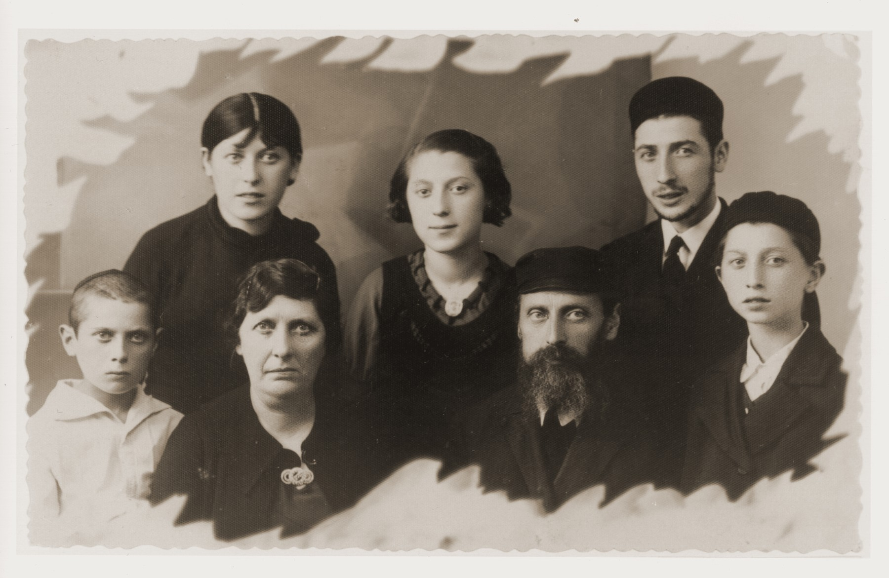 Portrait of the Tenenbaum family taken on the eve of Estera's departure for the United States.    Pictured in the first row, from left to right are: Fajwel; Anka Leah; Jonas and Szmuel.  In the second row are: Nechama; Estera and Srulik. The oldest brother is not pictured because he lived in Zdunska Wola with his family.