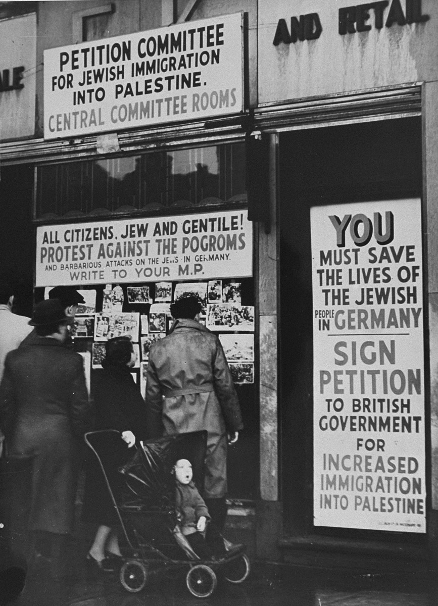 British Jews gather outside one of the offices in London's East End where signatures are being collected for a petition urging the Prime Minister to ease immigration restrictions to Palestine for persecuted Jewish refugees from Nazi-dominated central Europe.    Spectators view a display of photographs showing Jewish persecution under the Nazis that has been mounted in the front window of the office.