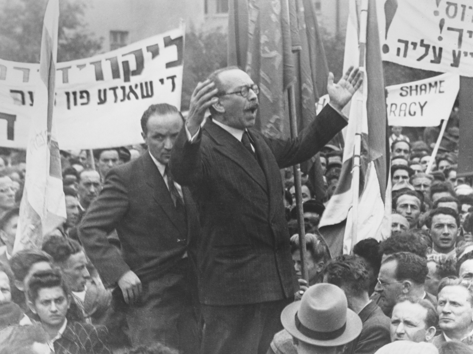 Marc Jarblum addresses a crowd of Jewish DPs at a demonstration in the Bergen-Belsen displaced persons camp that called for free immigration to Palestine and protested the return of the Exodus 1947 passengers to Germany.   Also pictured are Josef Rosensaft (standing behind Jarblum) and Norbert Wollheim (in profile on the right, near the front).