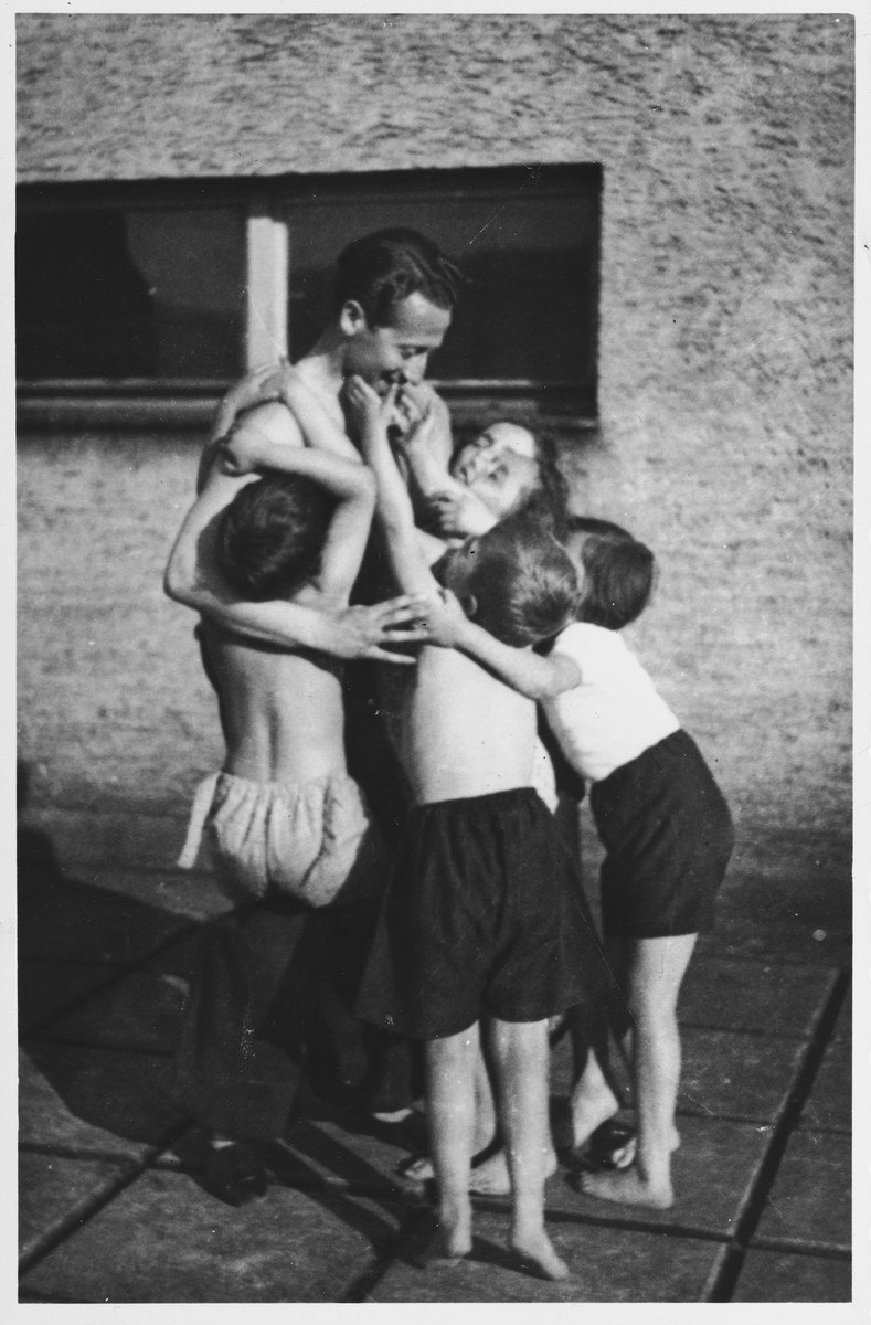Alex Hochhauser hugs a group of children in front of the Maccabi sports gymnasium in Zilina, Czechoslovakia.