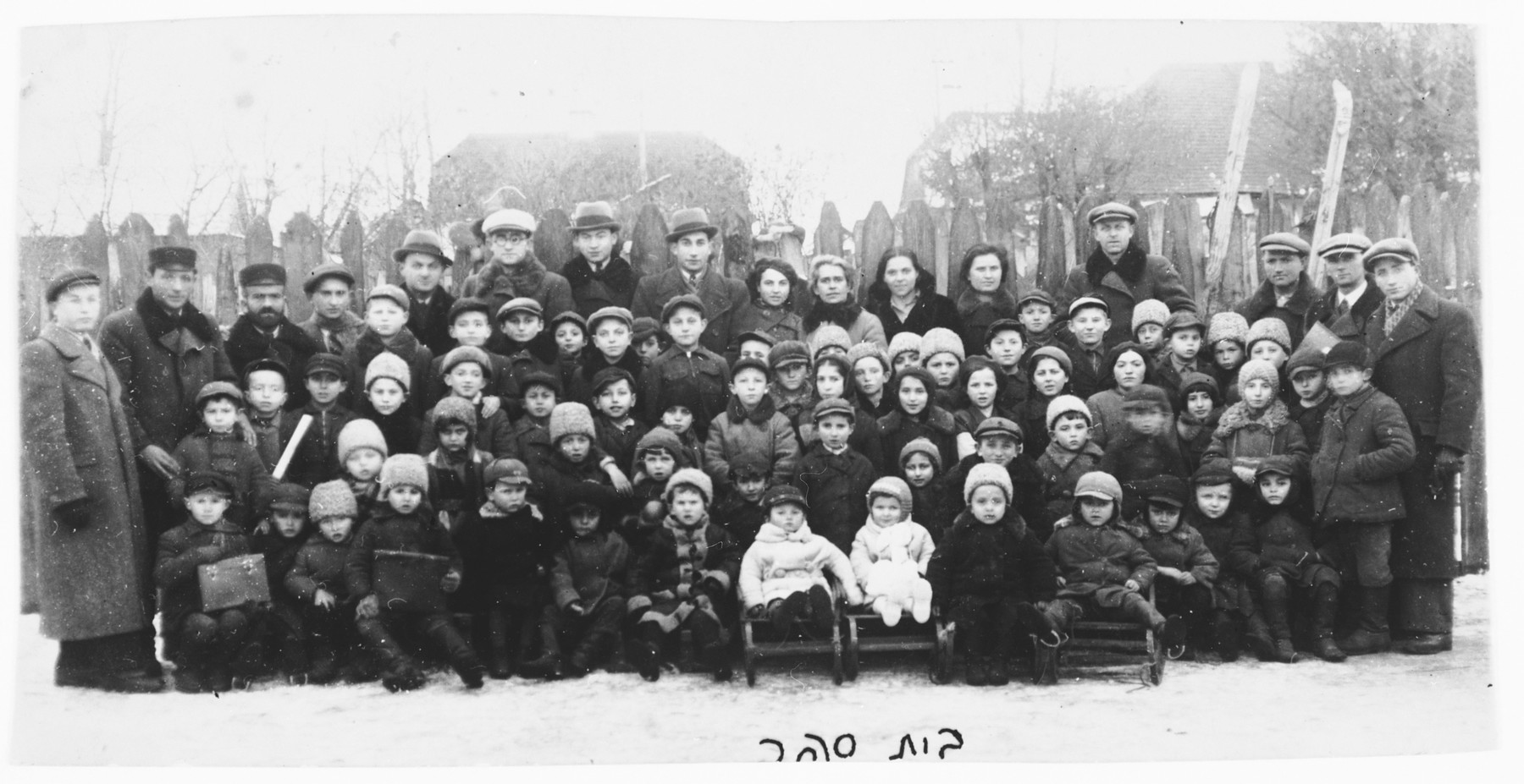 Students and teachers in the Hebrew school in Grabowiec pose for a group photo outside in the snow.  Lila Rajs is pictured in the front row, sixth from the right.