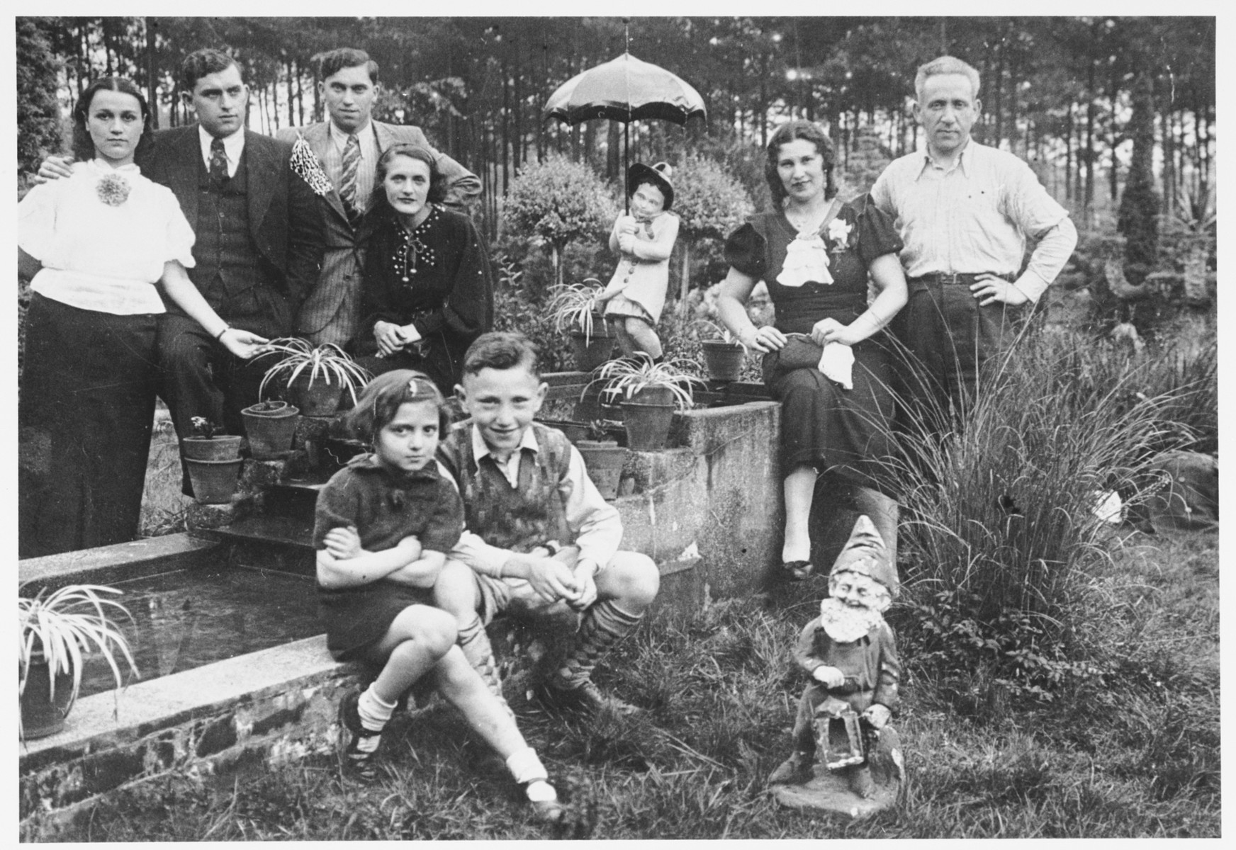Members of several Jewish families pose in a public garden in Antwerp, Belgium.  Pictured standing from left to right are Estera and Adolf Ciechanow; Alex and Leah Ciechanow; Chancu and Mendel Lublin. In front are Flora Mendelowicz and Jackie Ciechanow.
