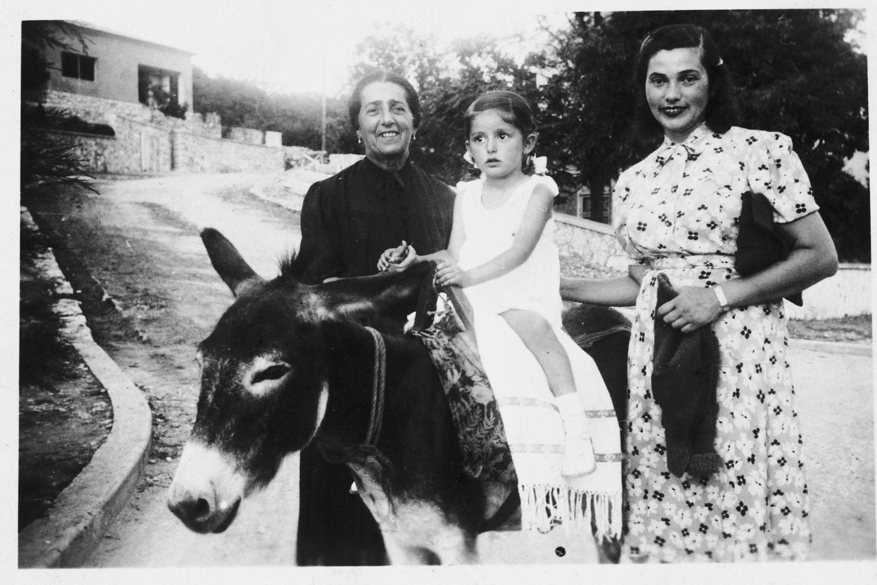 Branka Juhn rides a donkey while on vacation with her mother and grandmother on the Adriatic coast.  Pictured from left to right are: Flora, Branka and Henrietta Juhn.