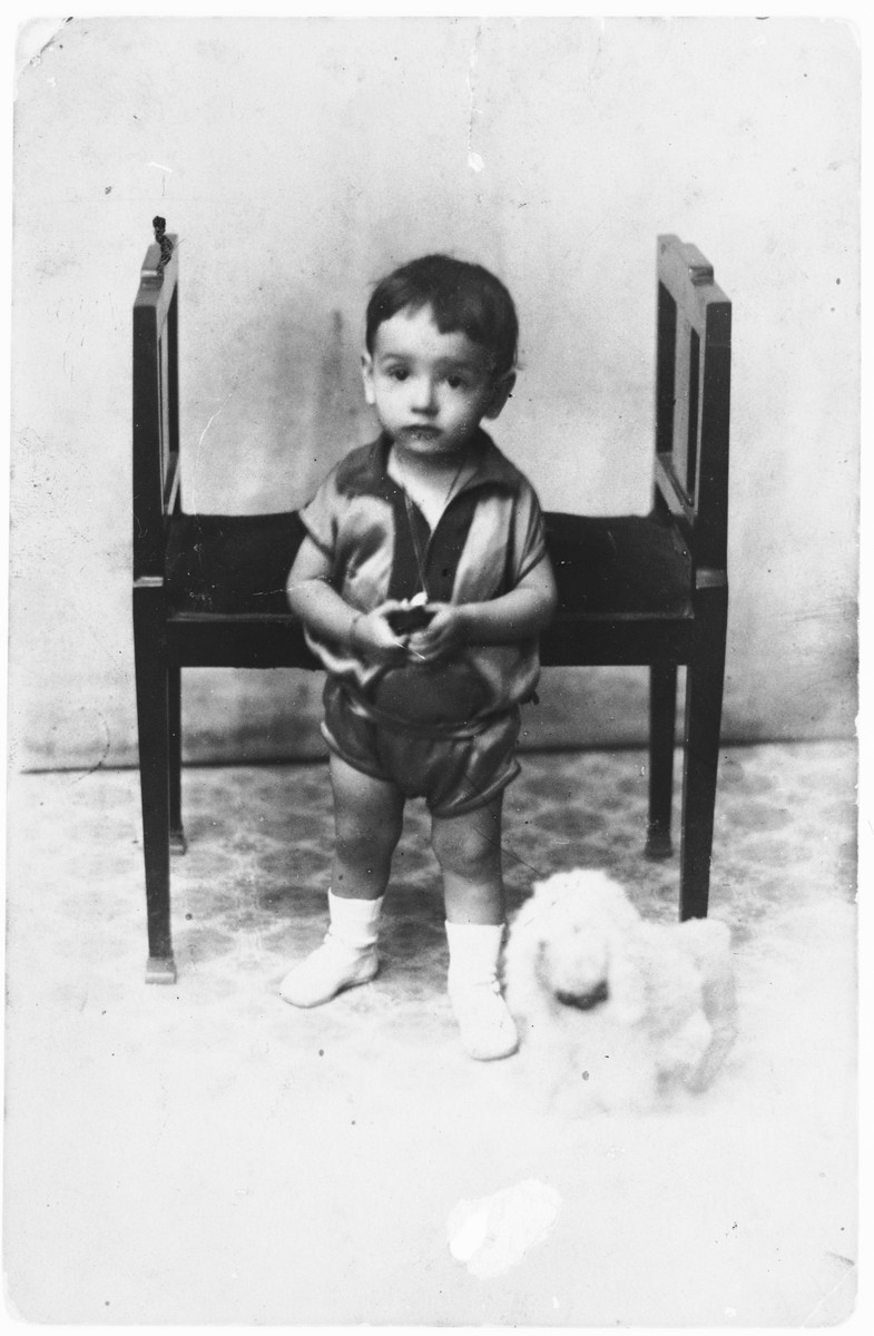 Studio portrait of Isaac Nehama with a toy dog at his side.