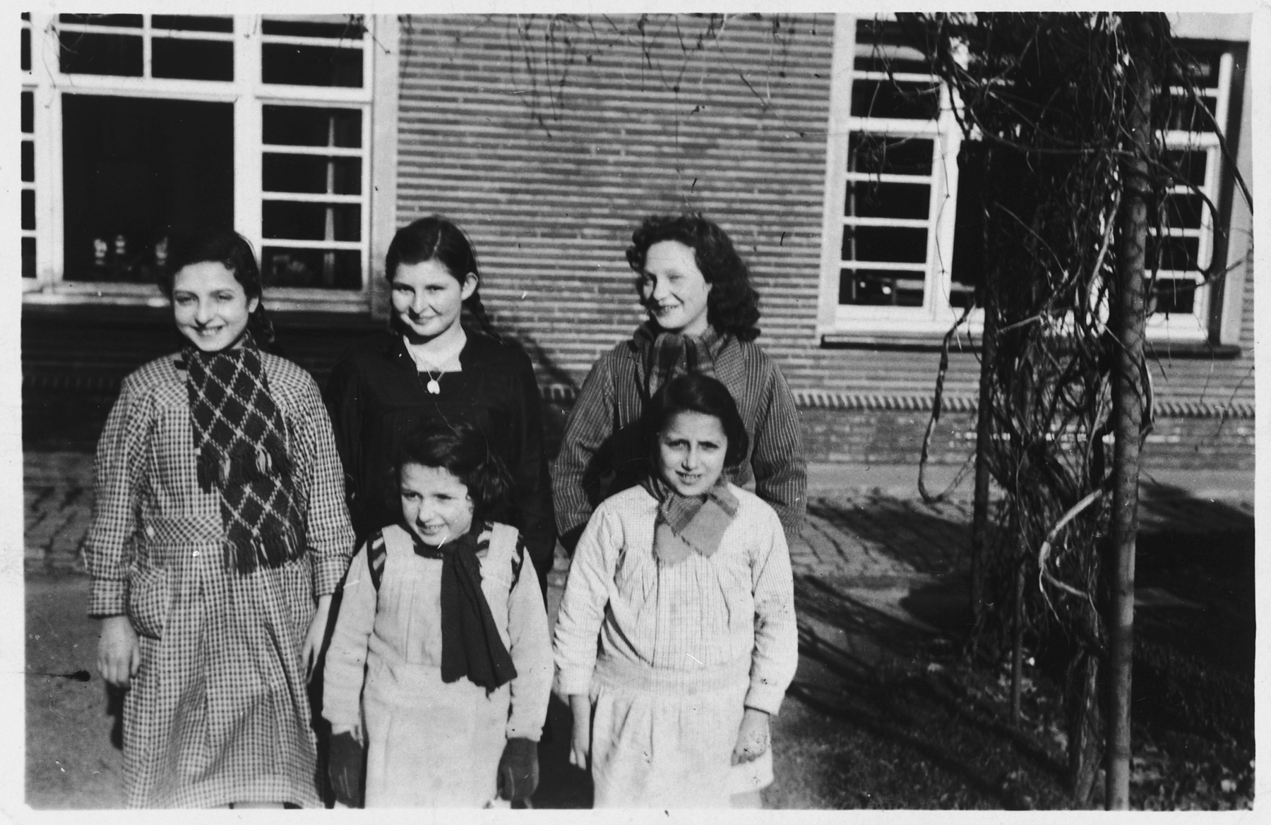 """Group portrait of Jewish girls living in hiding at the """"Our Lady of Seven Sorrows"""" convent in Ruiselede, Belgium.  Pictured in front from left to right are: Betty and Charlotte Mendelowicz.  Behind them are Flora Mendelowicz, Ruth Wallach and Paulette (last name unknown)."""