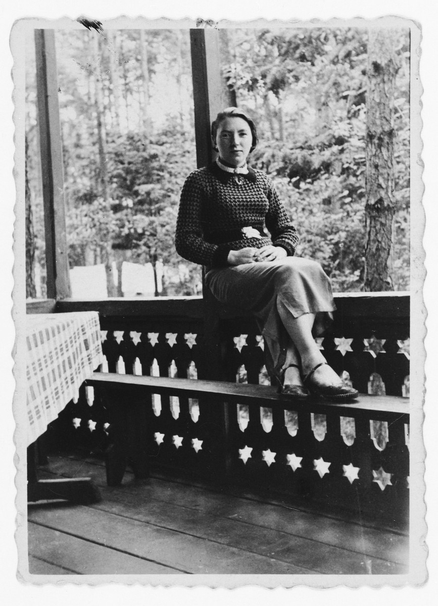 Toby Papier (the donor's aunt) sits on a porch railing overlooking a woods.