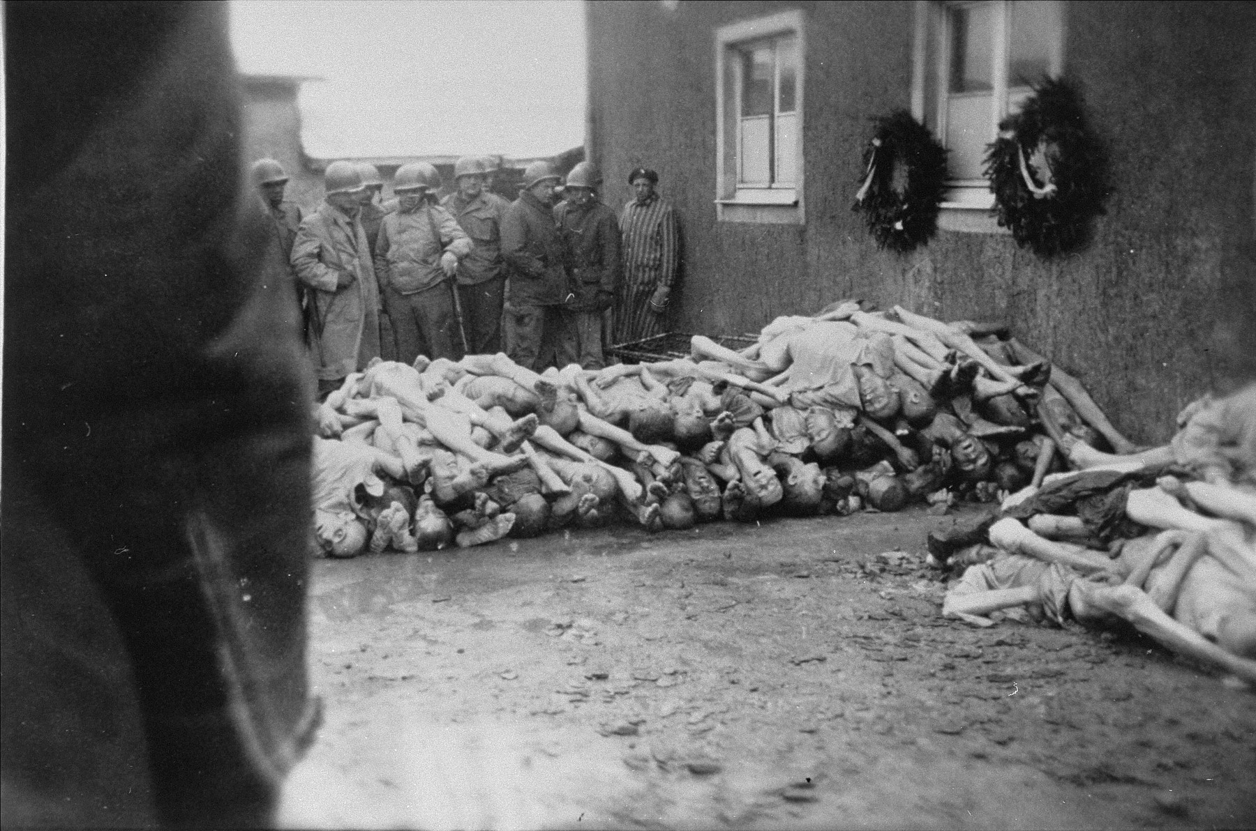 Survivors and American soldiers look at a pile of corpses behind the crematorium in Buchenwald.