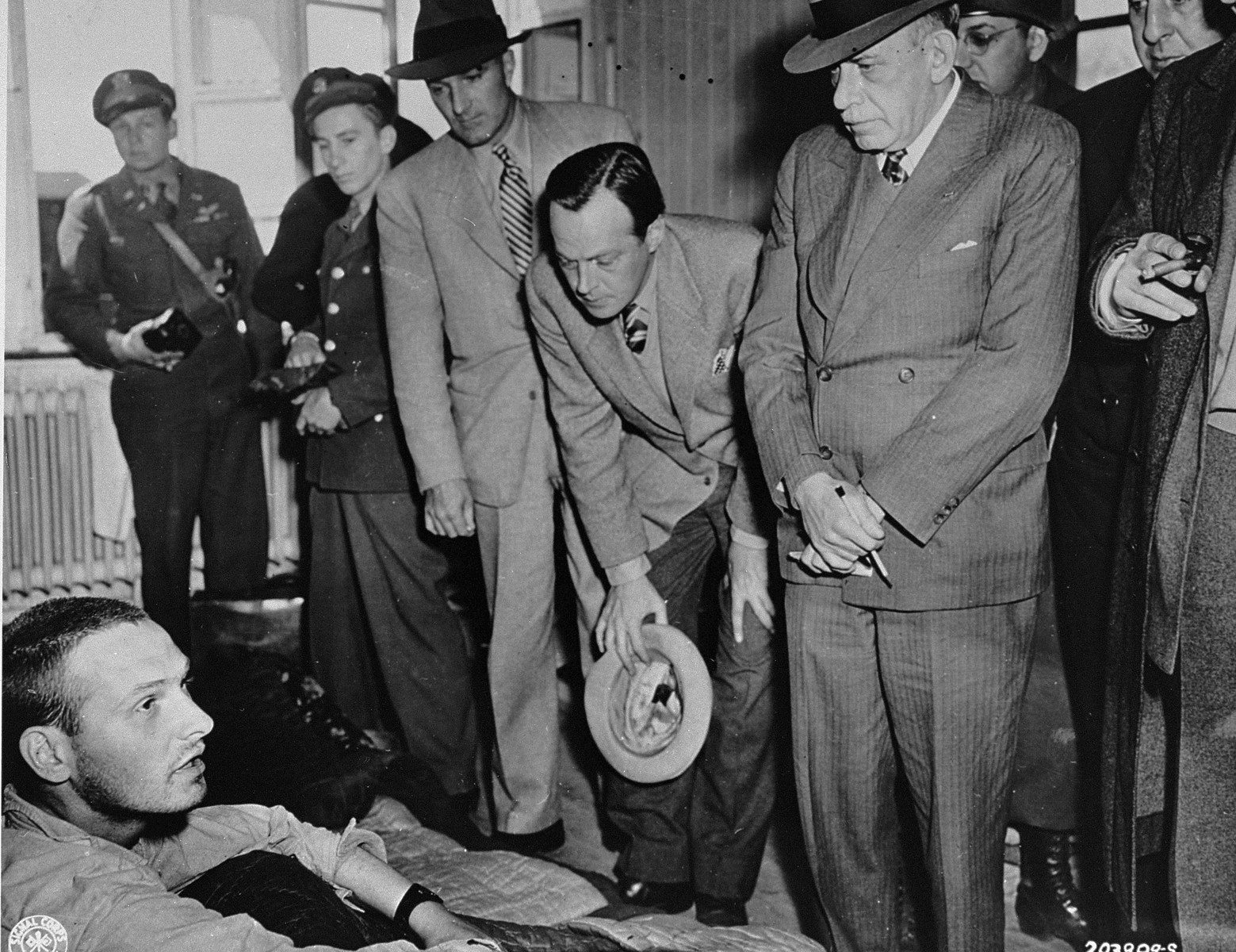 American newspaper editors visit a hospital in the newly liberated Buchenwald concentration camp to speak with survivors about the crimes they witnessed.    Pictured from left to right are: Norman Chandler of the L. A. Times, William I. Nichols of This Week Magazine, and Julius Ochs Adler of the New York Times.