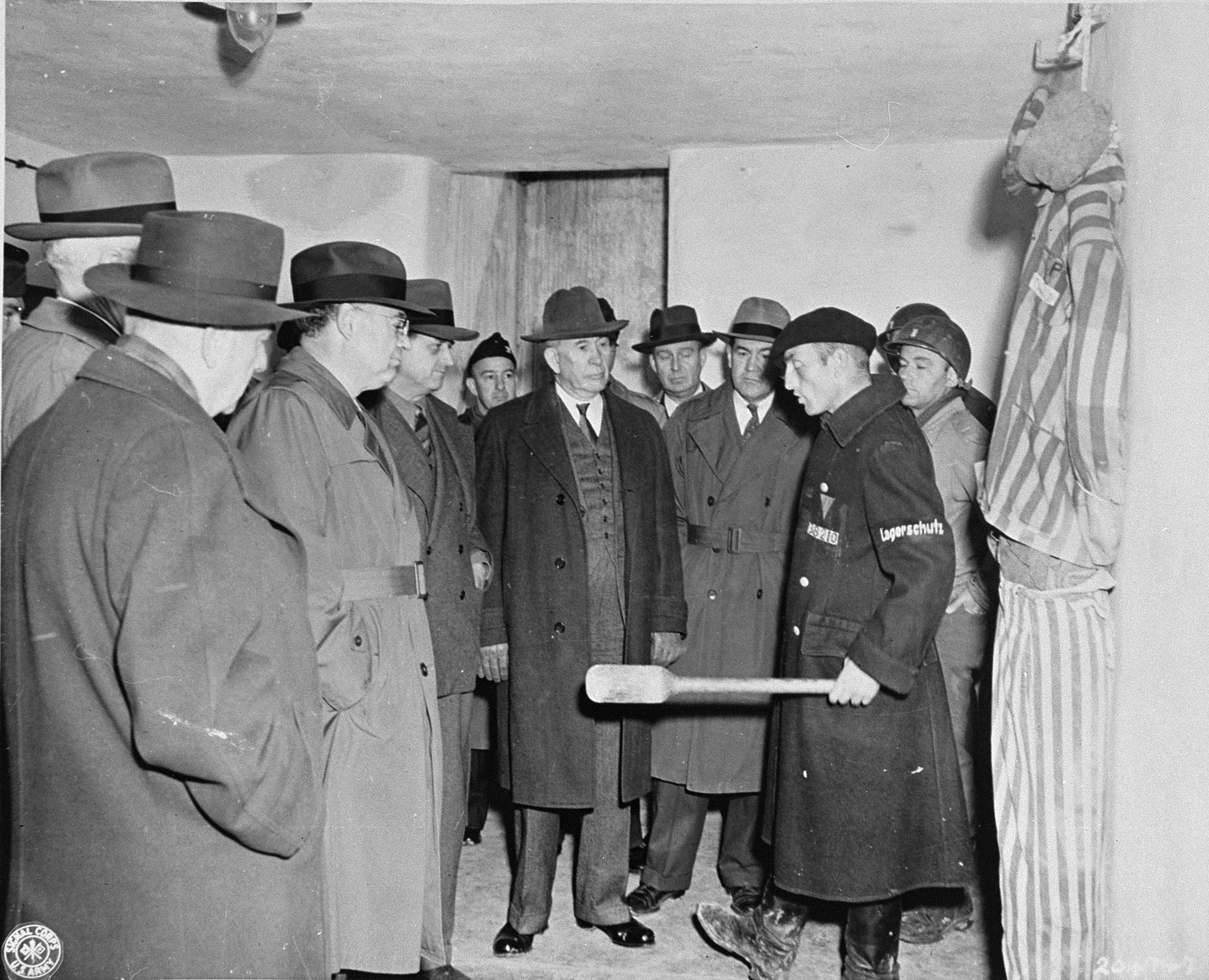 A survivor demonstrates SS methods of torture and execution in Buchenwald to a visiting delegation of American congressmen.